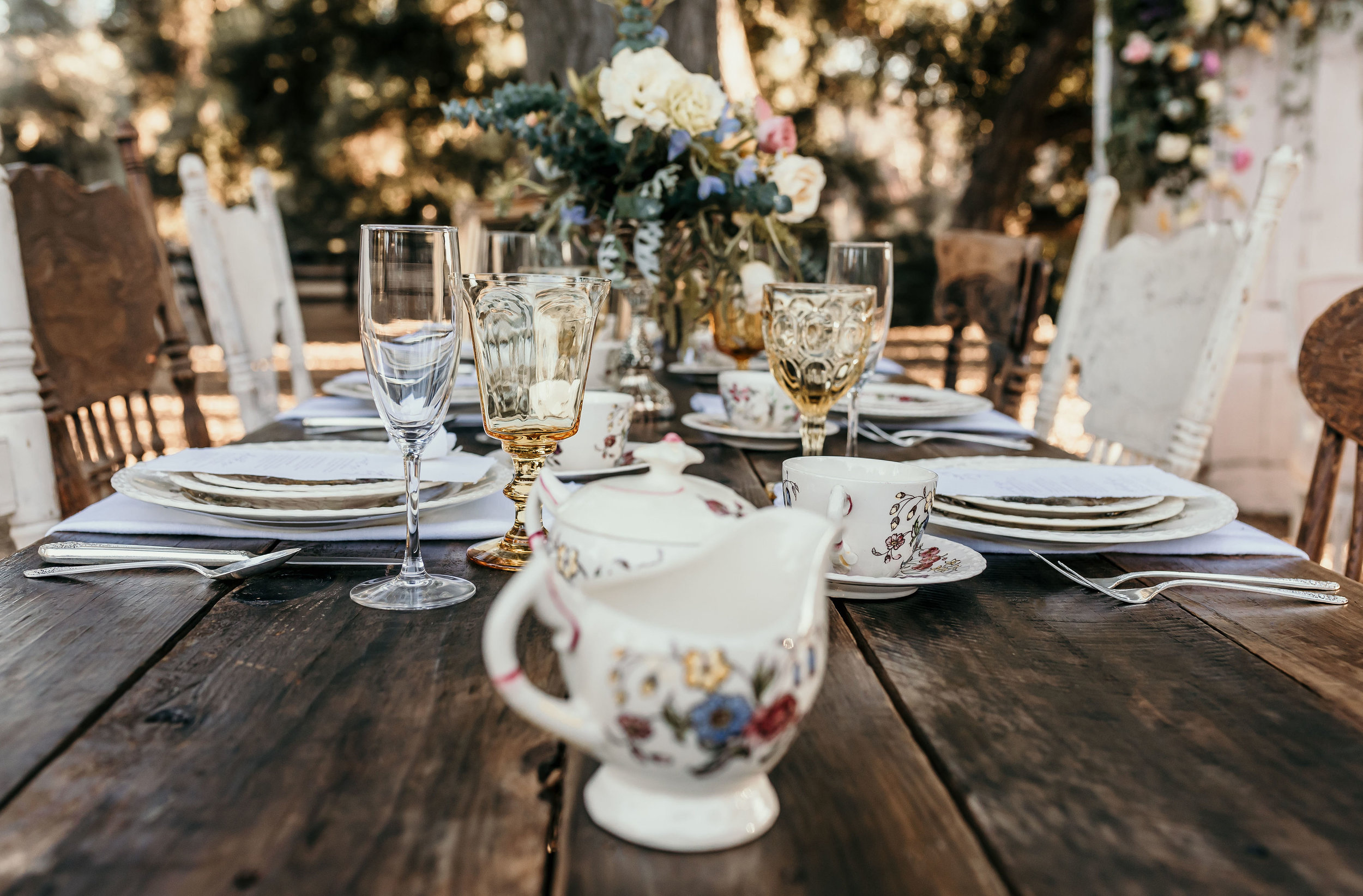 Vintage china and crystal goblets set on a farm table waiting for the wedding party to arrive. This was provided by Birdie in a Barn in Murrieta.