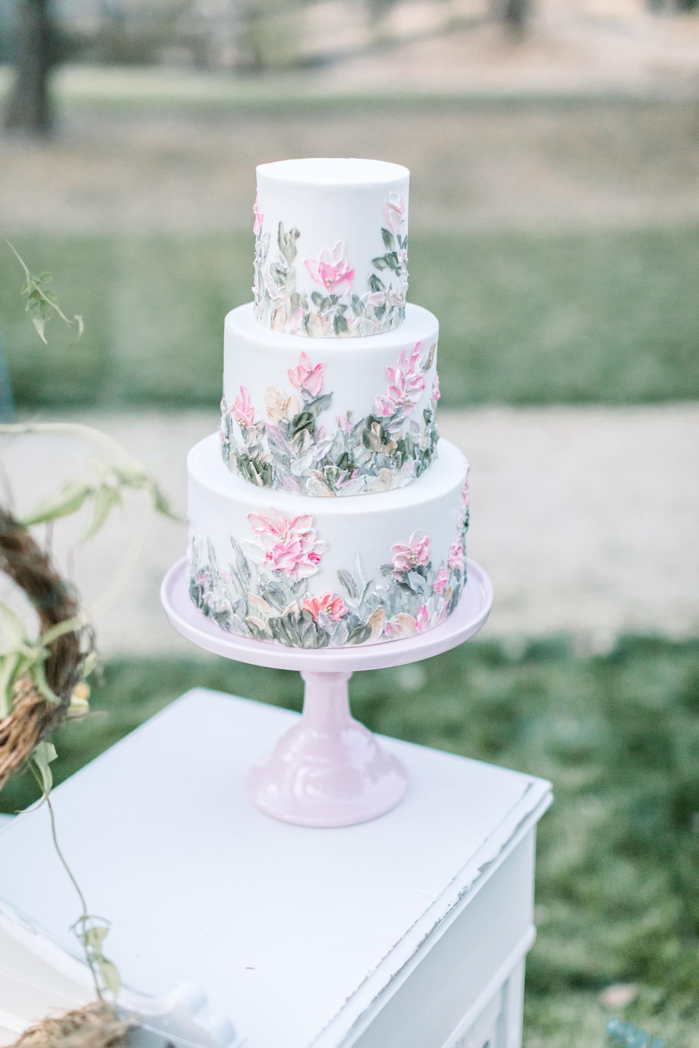 Pink Wedding cake on a pink pedestal cake plate.