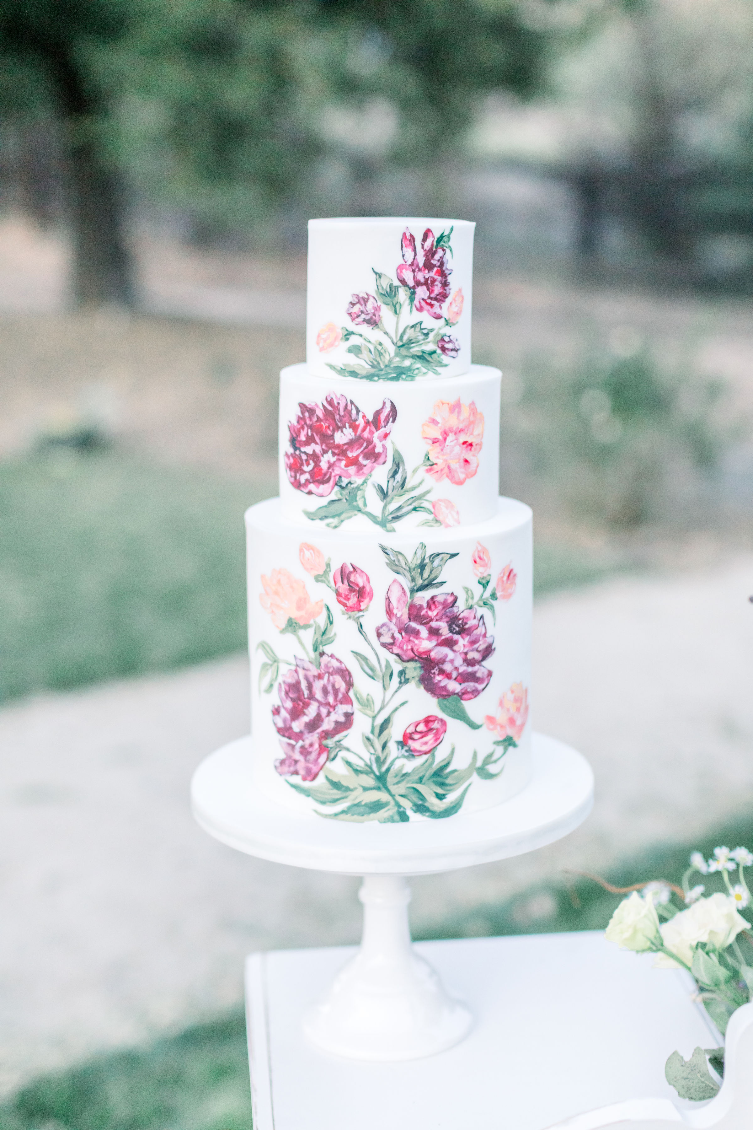 A hand painted floral wedding cake in pink tones. Three tiered white base frosting. White pedestal.