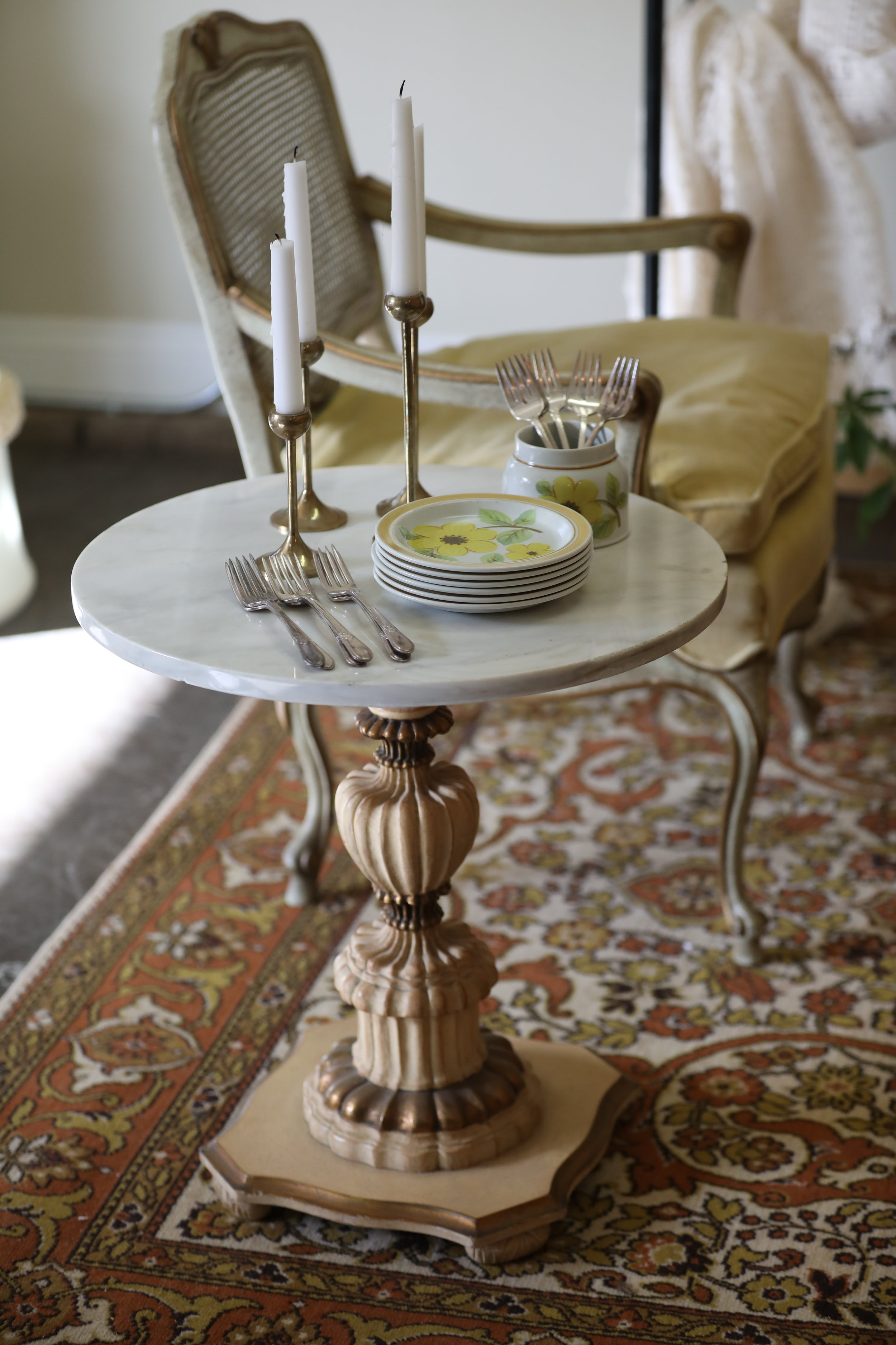 Vintage furniture for rent from Birdie in a Barn in Murrieta.  Hollywood regency side table and French provincial chair with vintage rug.