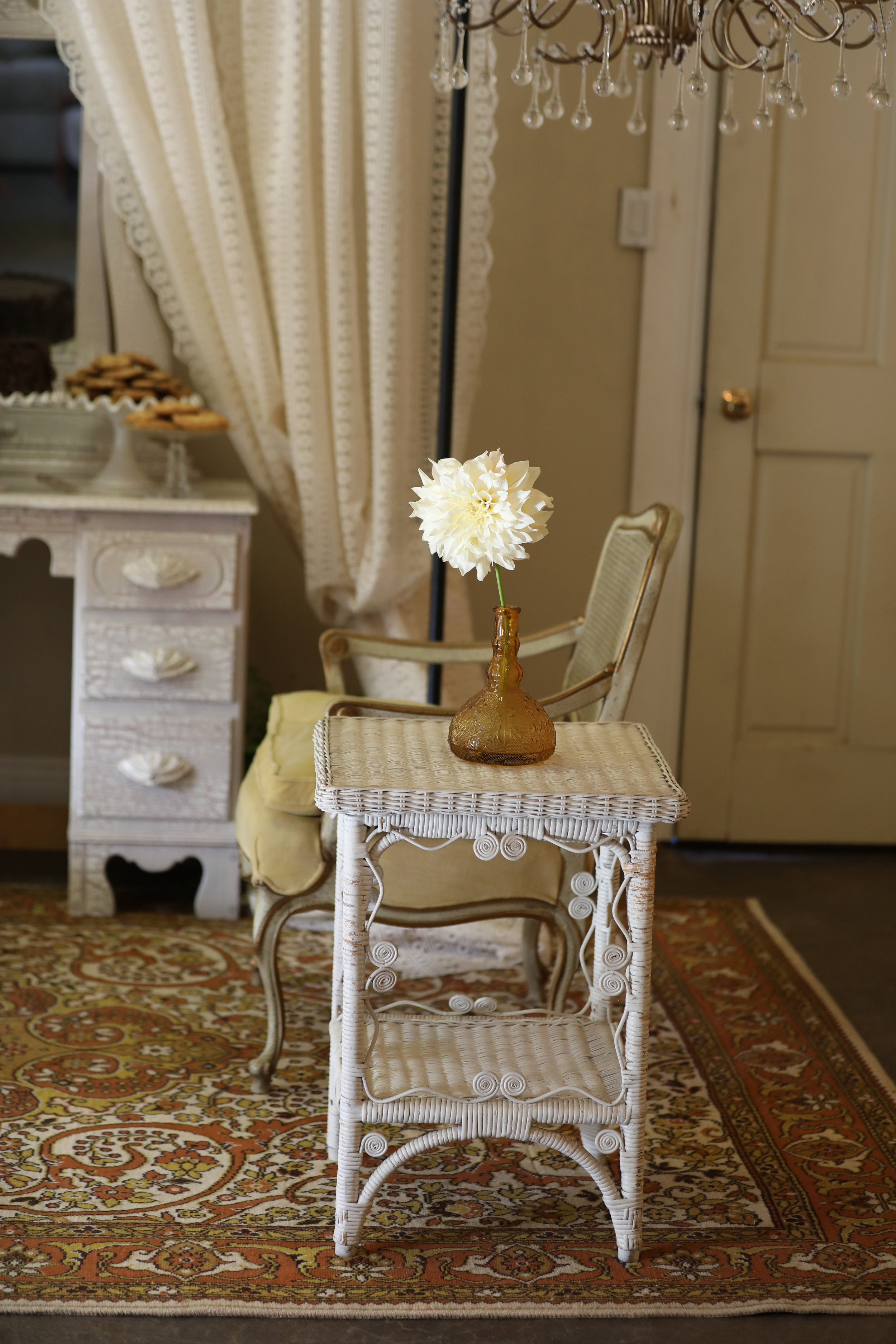 White wicker side table with French provencal gold velvet chair.