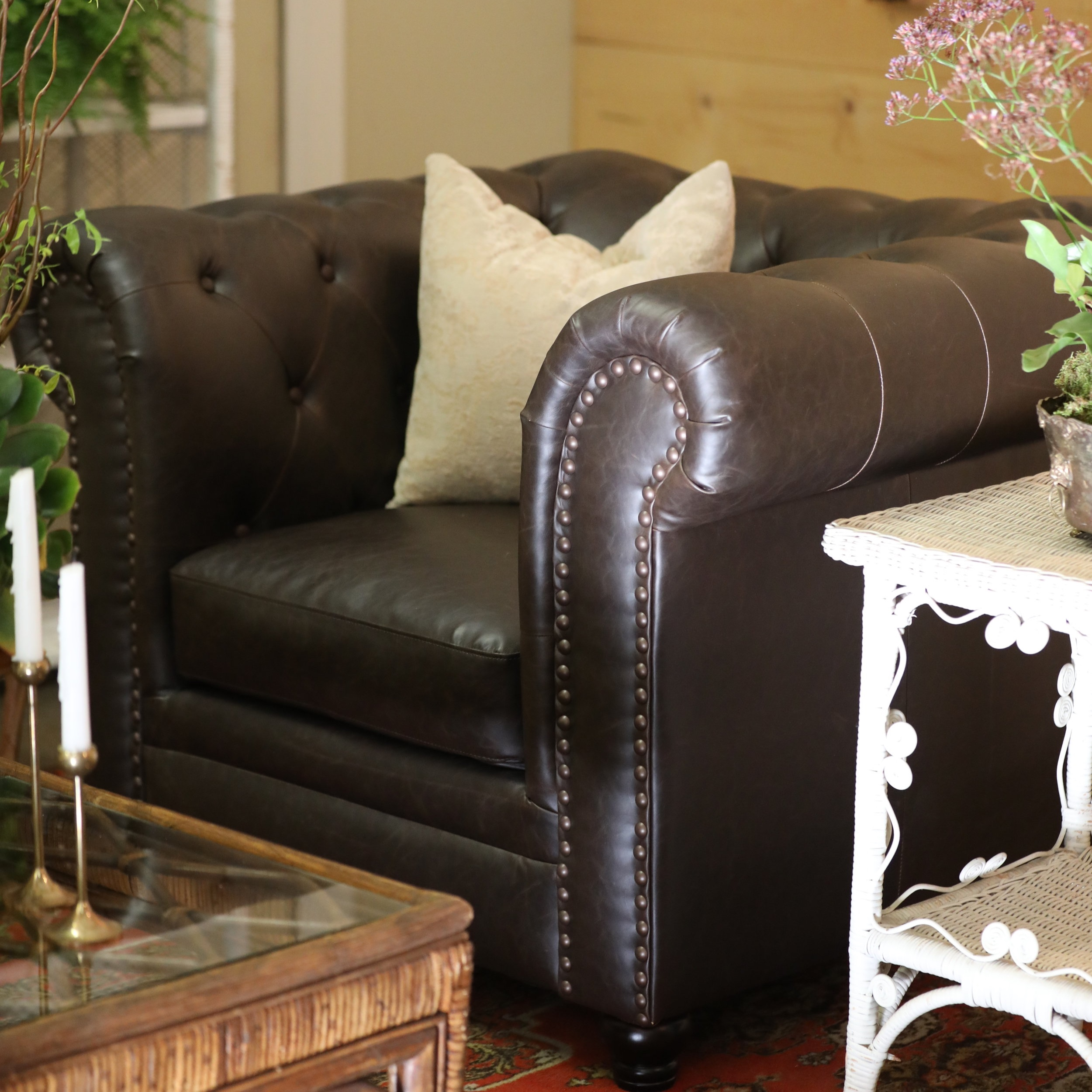 Renaldo   Brown leather square chair with a tufted back and arms.