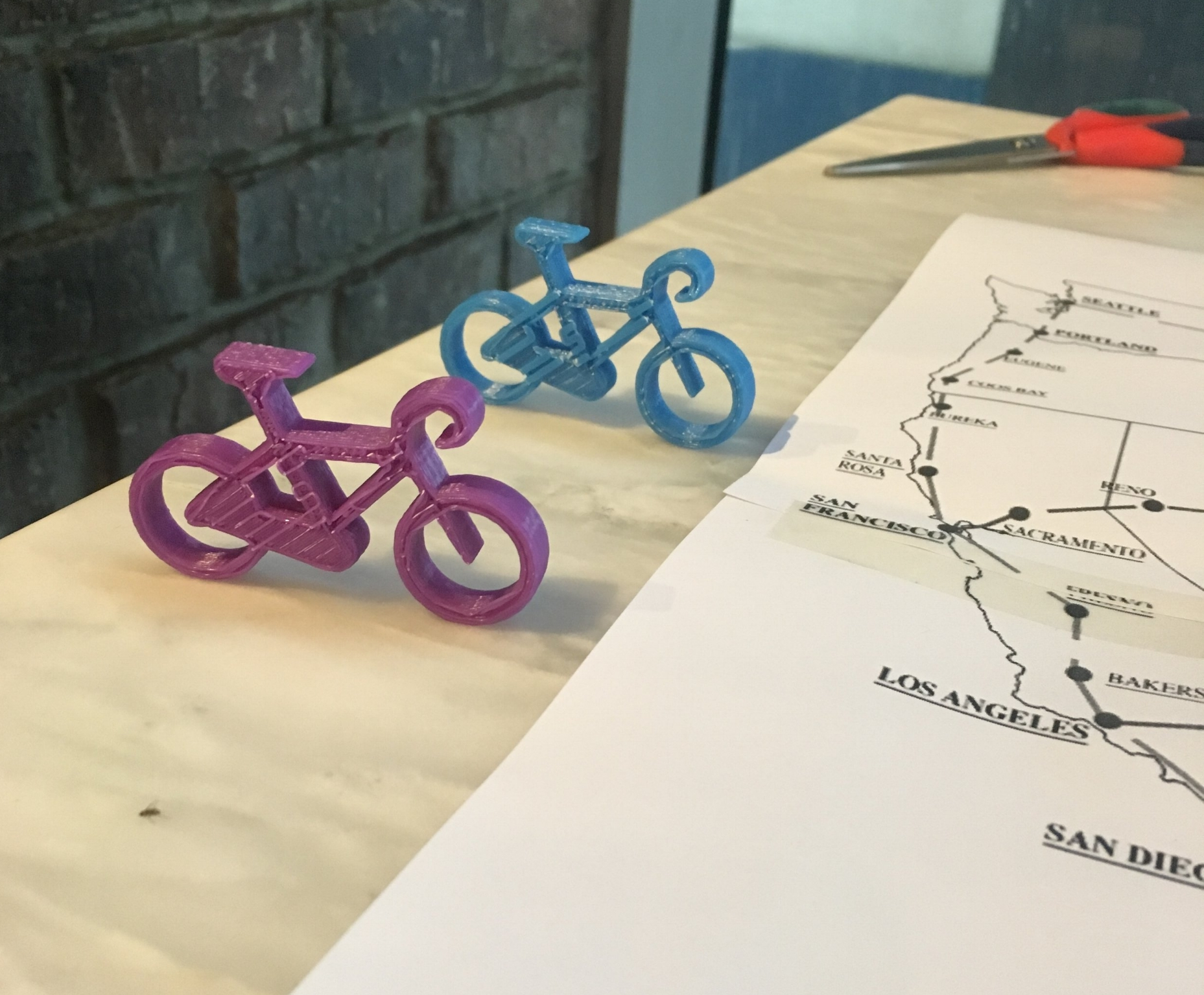 The first playing pieces! Got a 3D file of a bicycle from GradCad.com and used our school's 3D printing machine to print them out (we are both teachers).
