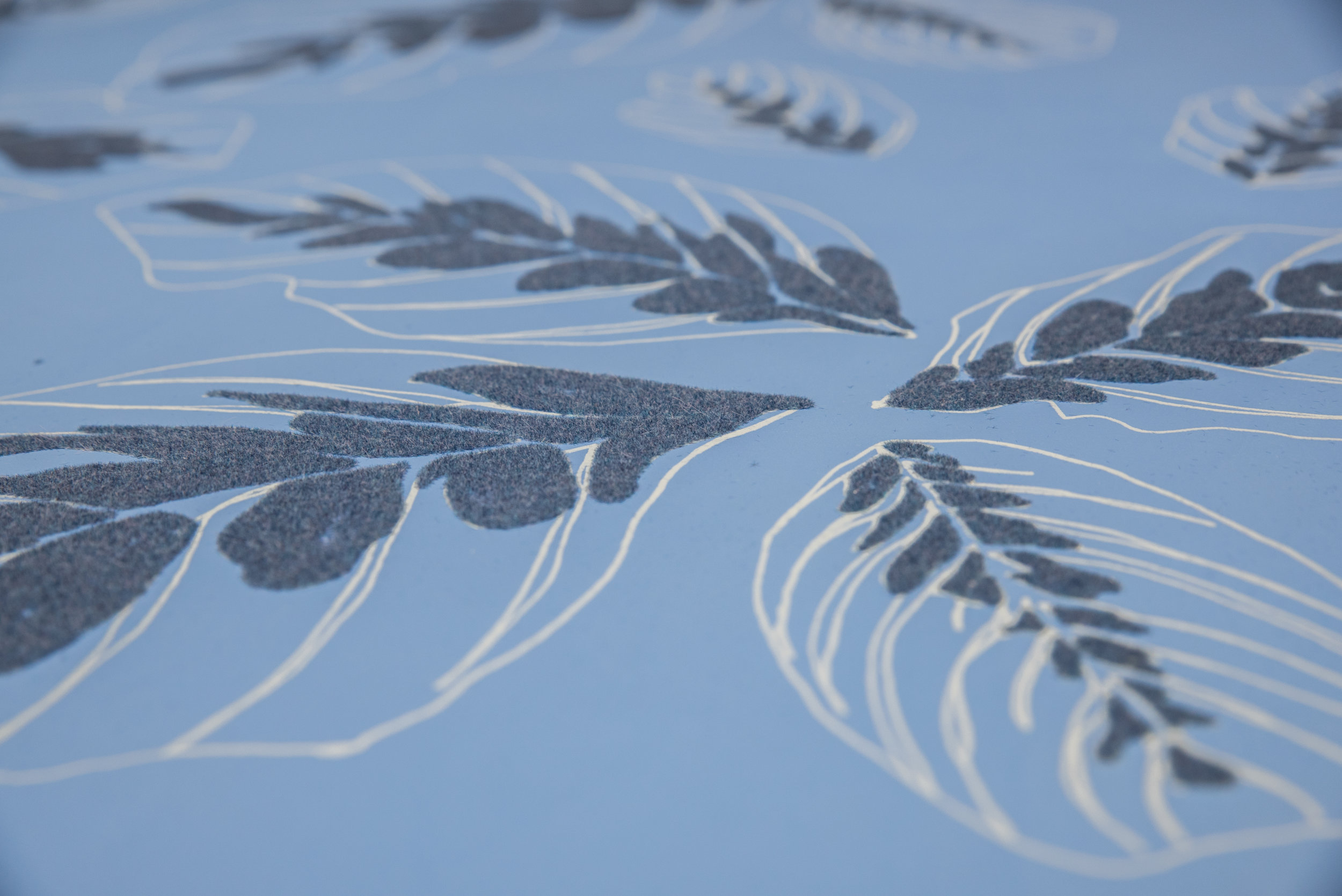 Blue exotic plant leaves. Hand drawn, screen printed motifs in repeat, flocked and screened on to wallpaper.