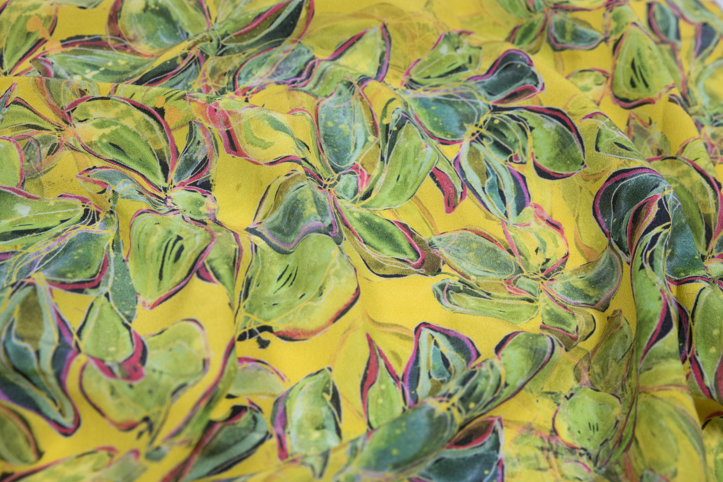 Vibrant cacti leaves on yellow silk chiffon.