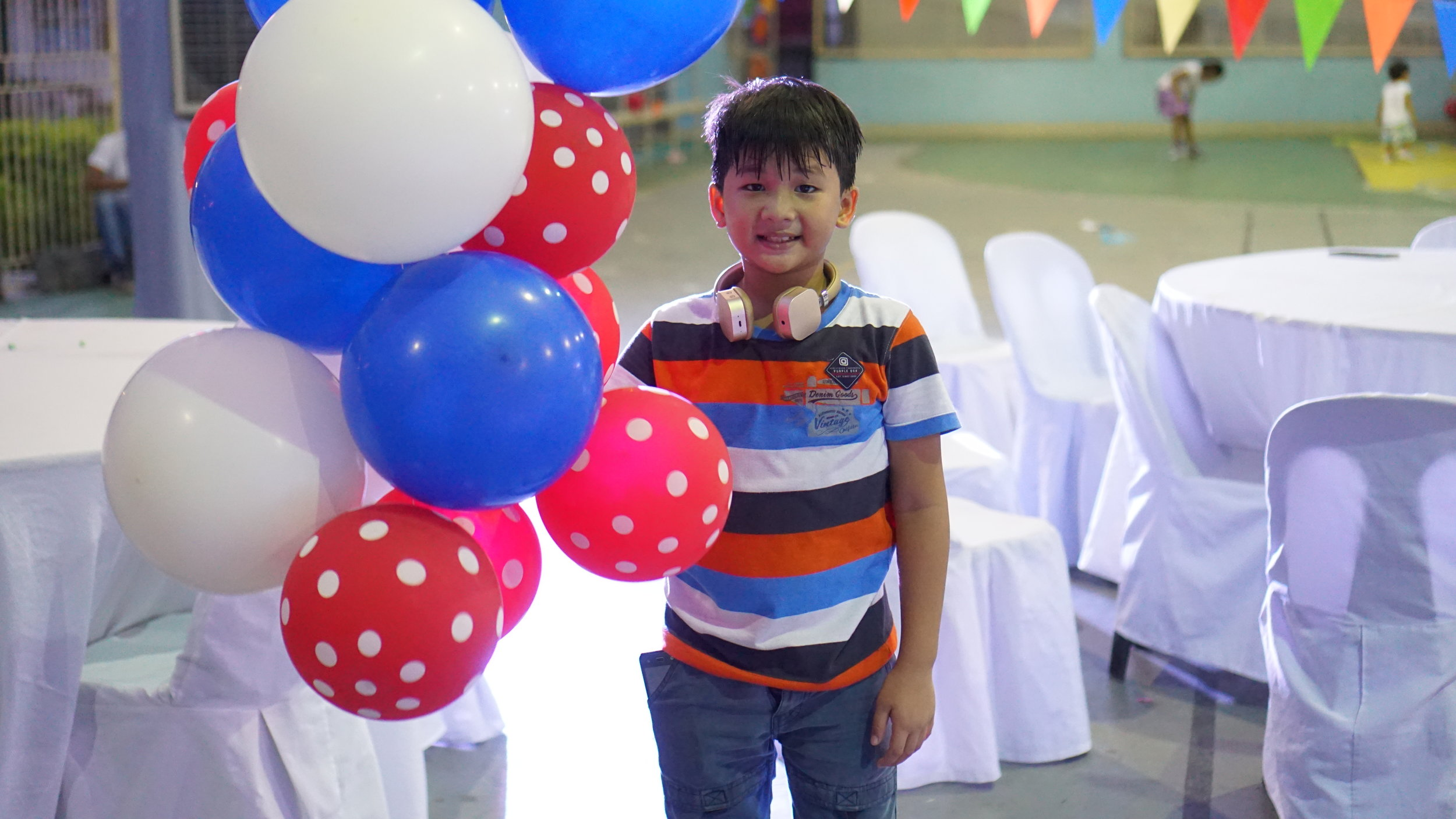 My cousin, Gabo. Blue, red, and white balloons (Philippine flag colors) tied all around the basketball court and popped or taken home by the kiddies. :)