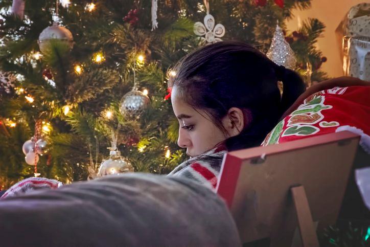 girl-relaxing-next-to-a-Christmas-tree-657457148_727x484.jpg