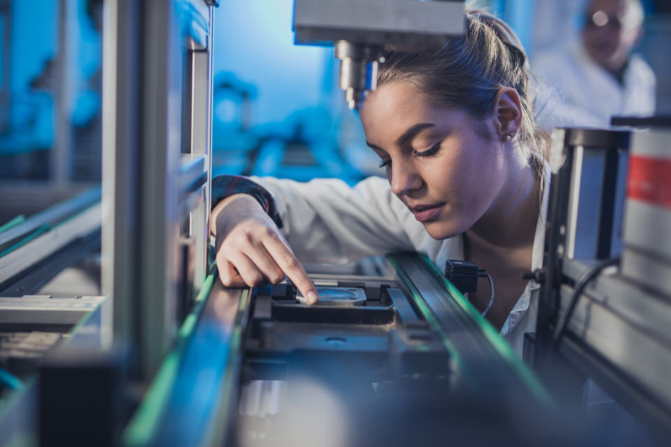Female-engineer-examining-machine-part-on-a-production-line.-681697244_2125x1416.jpeg