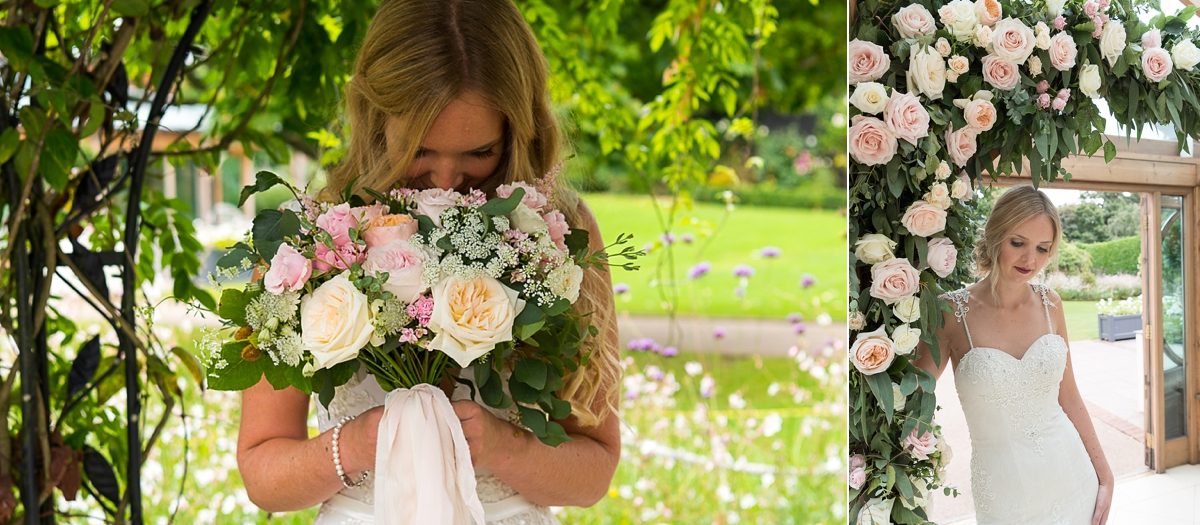 Bride holding bouquet of roses and standing in rose archway at Gaynes Park