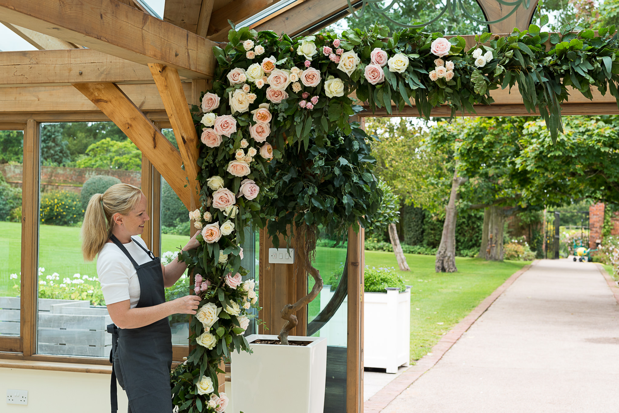 Half arch floral installation with cream and pink roses and foliage at Gaynes Park.
