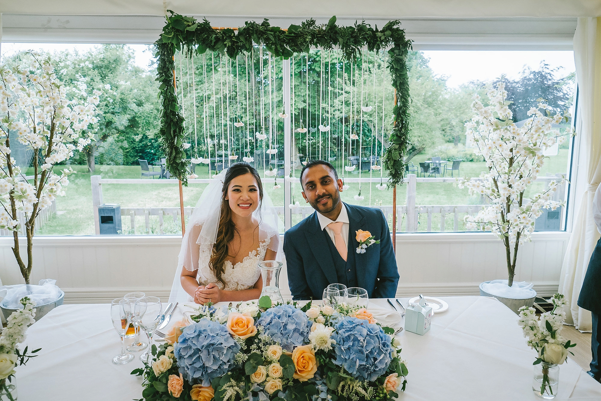 Sweetheart table at Essex garden wedding with peach and blue floral arrangement and hanging carnations on copper frame