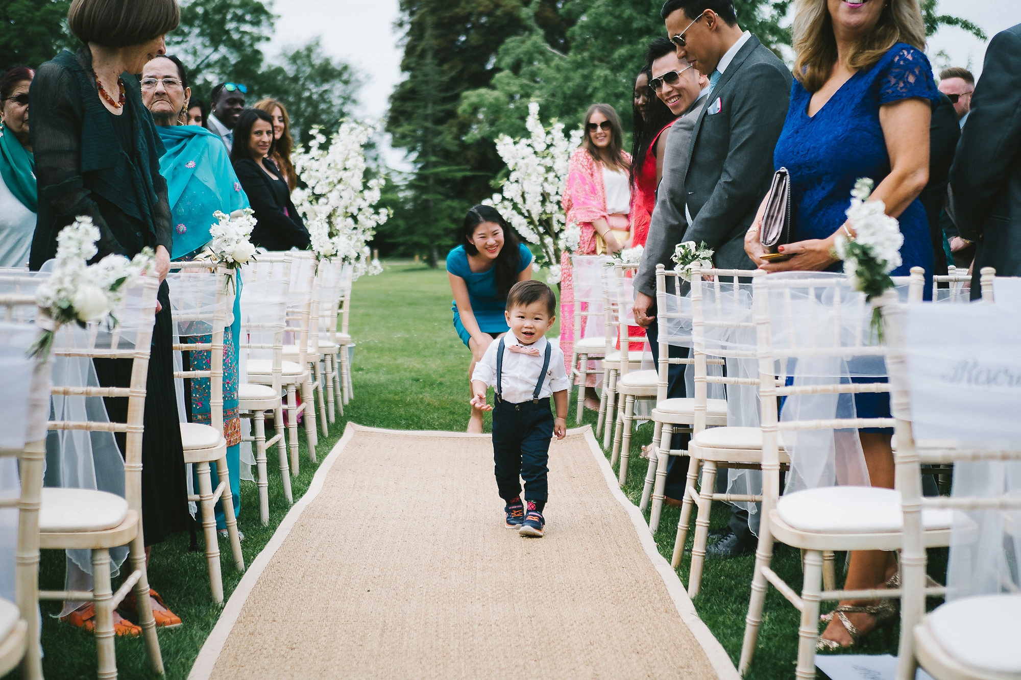 Young page boy runs down the aisle at an outdoor wedding ceremony at The Fennes