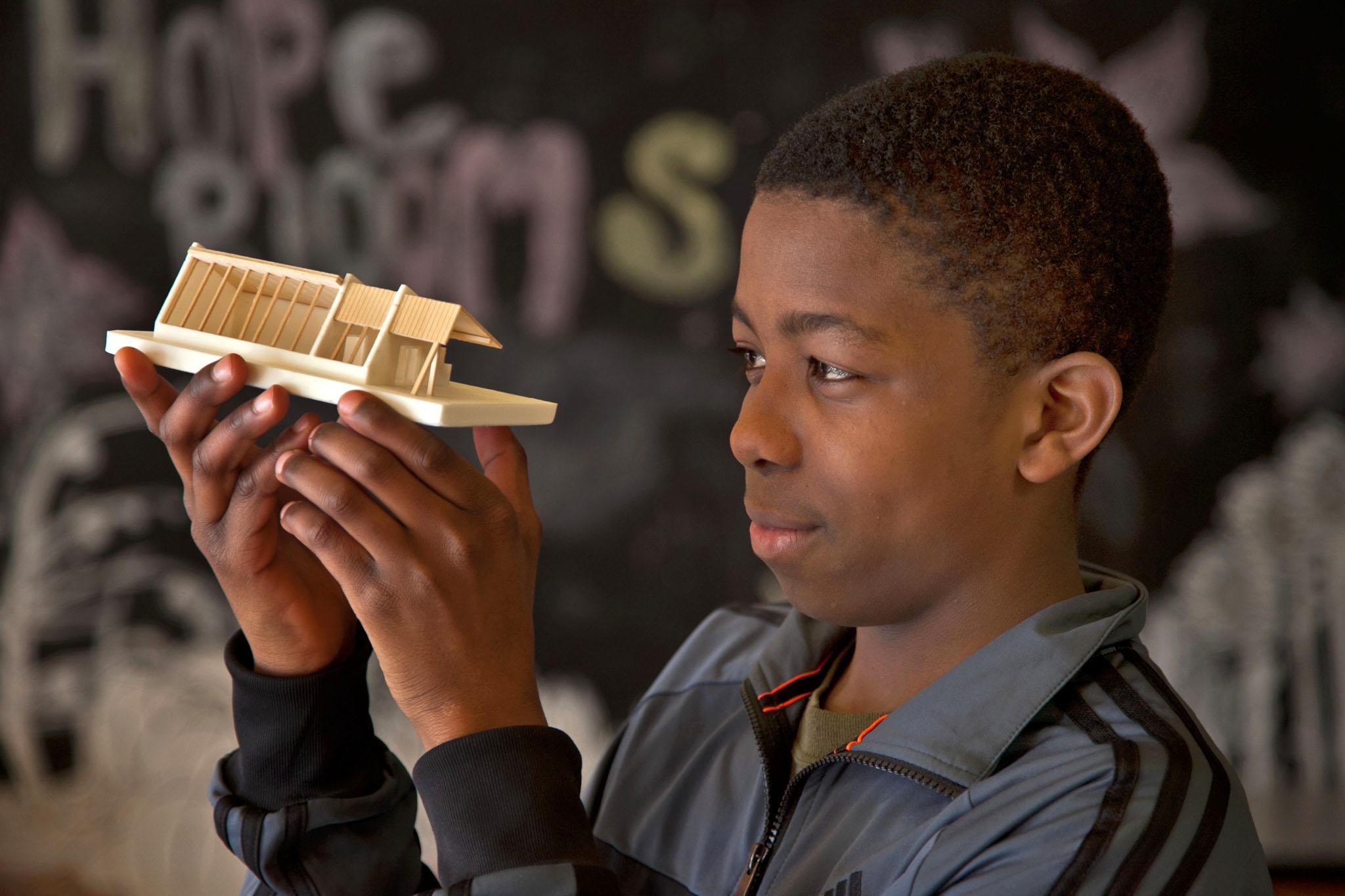 Kolade Boboye examines a model of the greenhouse.