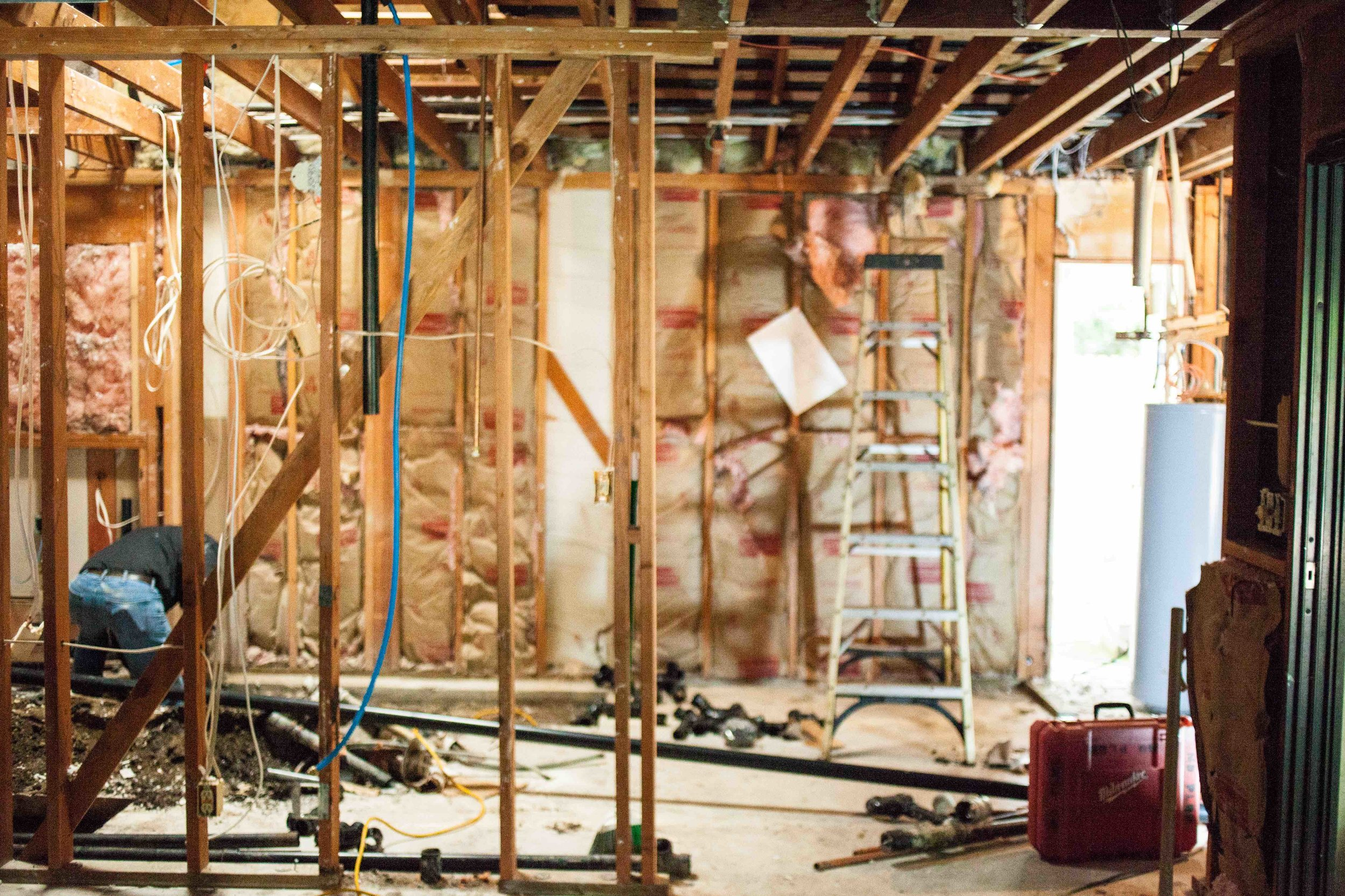 WHAT ARE YOU LOOKING AT?   1.  FOREGROUND : EXISTING MASTER BEDROOM 2.  STRAIGHT AHEAD & TO THE LEFT: CONCRETE TRENCHING TO PREPARE FOR PLUMBING CHANGES 3.  CENTER : PLANS ATTACHED TO THE STUDS...SEEING THIS ALWAYS MAKES ME HAPPY! 4.  FAR LEFT:  WATER HEATER AND OLD CLOSET STORAGE