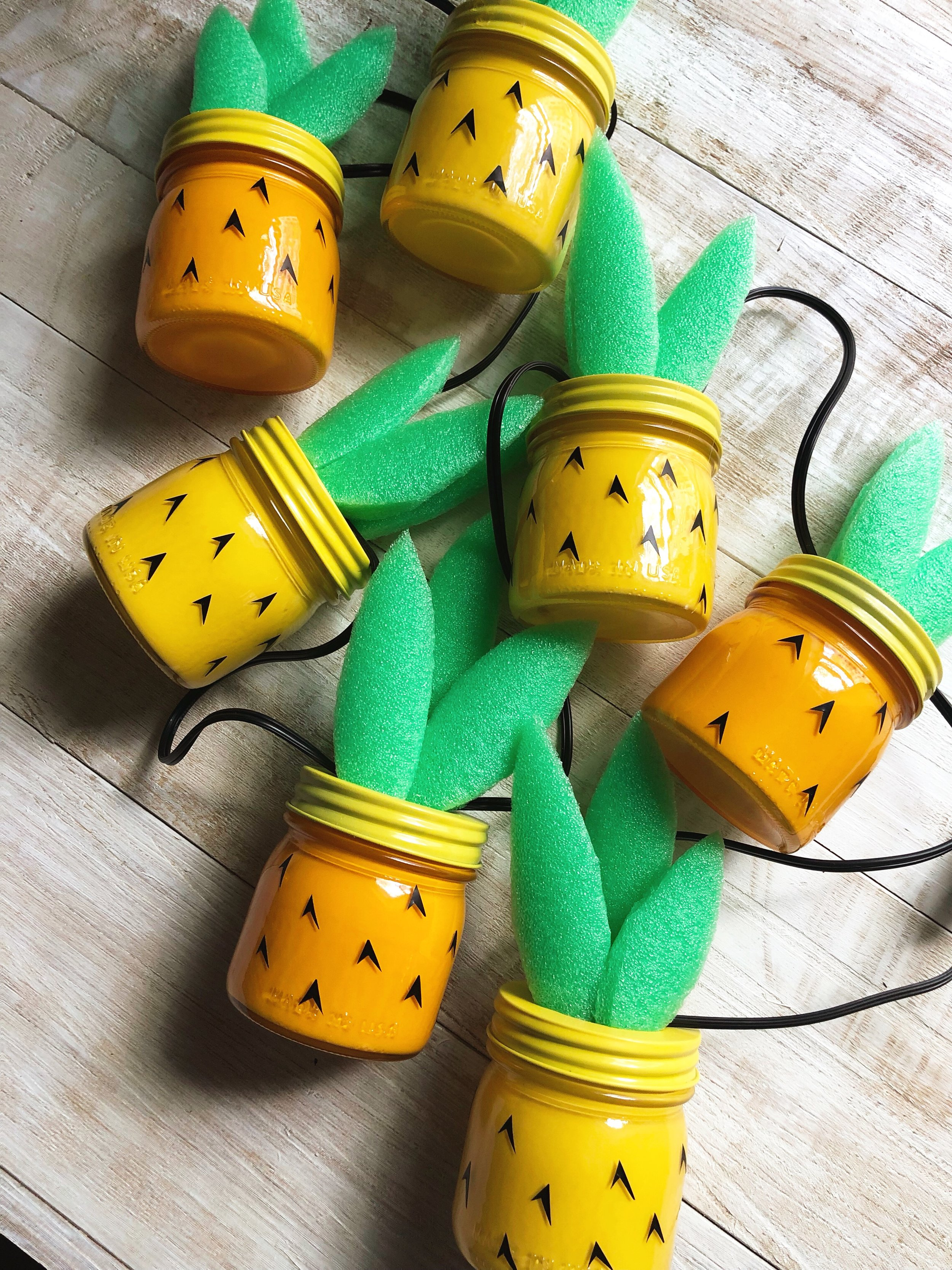 DIY Pineapple Jar String Lights! Use mini @Ballcanning jars to create a tiki inspired strand of pineapple lights! Summertime and the crafting is easy! @MichaelsStores #Balljars #masonjars #pinapple #pineapplecraft #tiki #tikilights #tikicraft #barcraft #summerdiy #summercraft #pooldecor #poolnoodlecraft #poolnoodle #Acrylicpaint #Tropicalcraft #tropicallights #summerlights #madewithmichaels #michaels