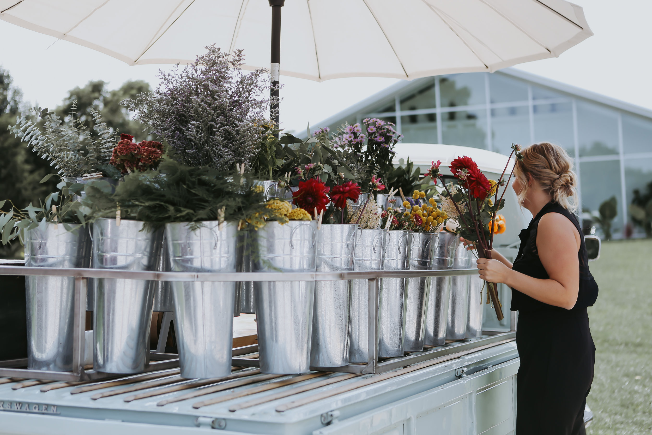 A bride makes the bouquet for her partner at Ozark Mtn. Flower Truck's flower bar brought to the venue.