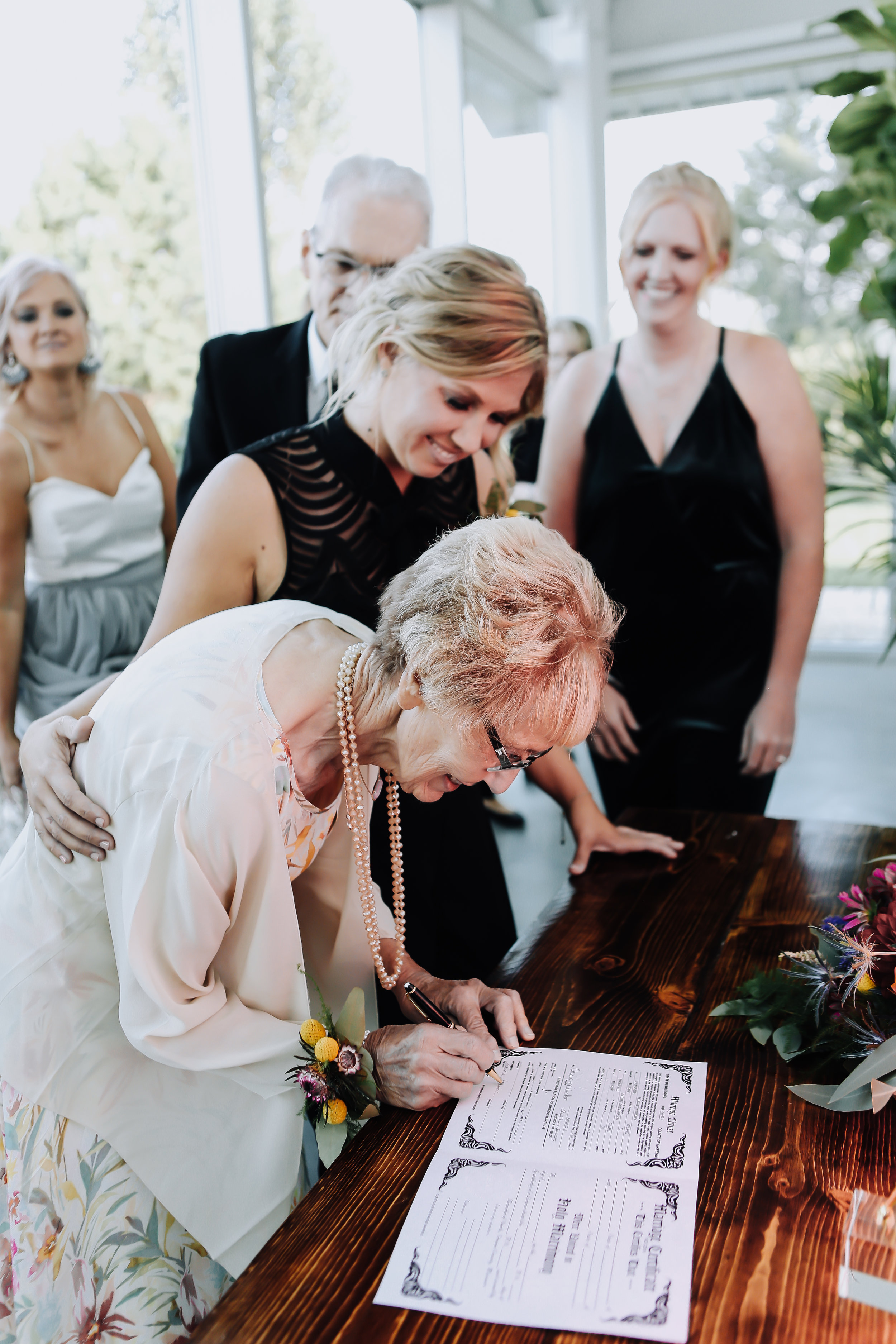 Bride chooses her grandmother as a witness to sign the marriage licenses. | Greenhouse Two Rivers | Unions With Celia inclusive wedding planner