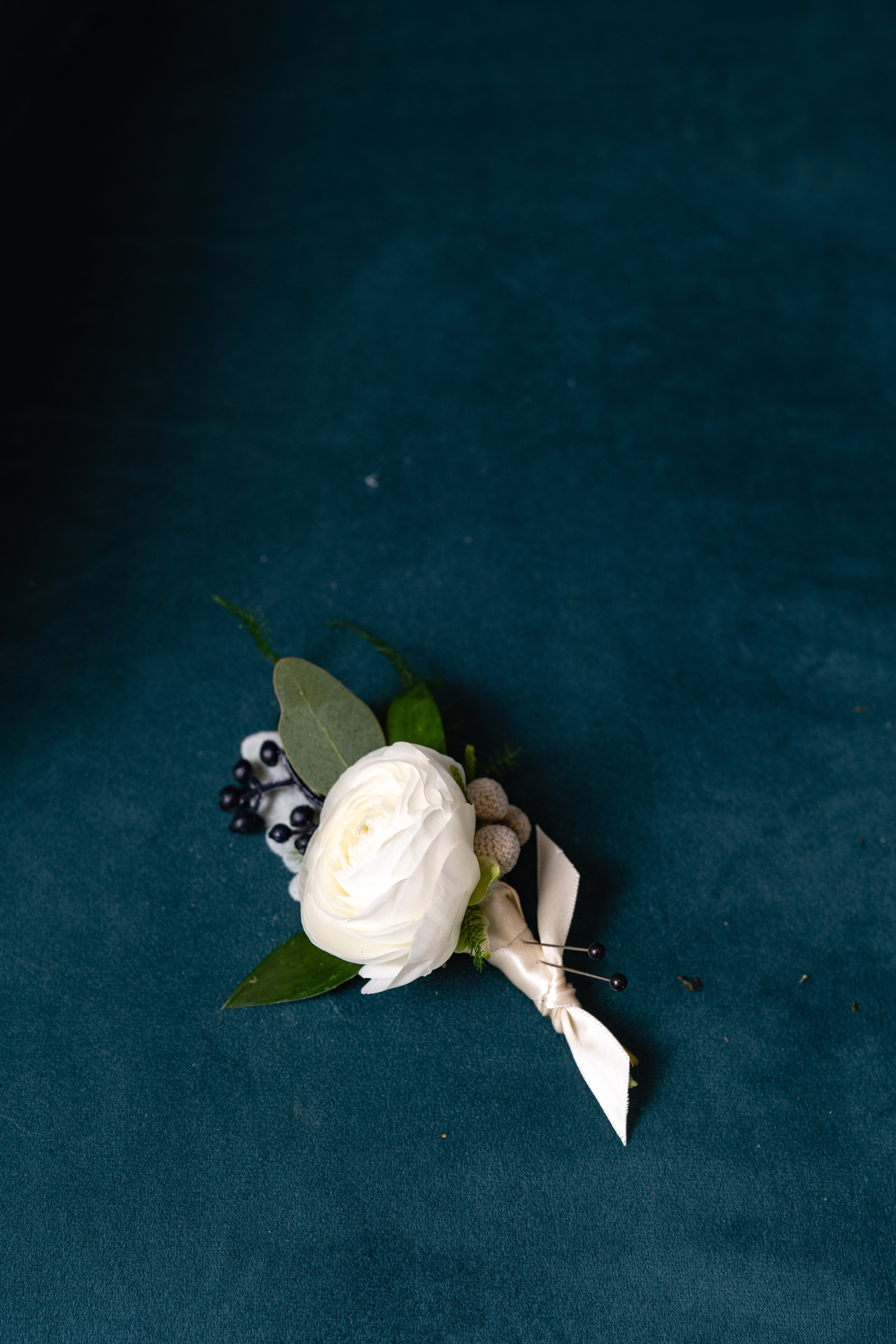 A simple, white boutonniere is perfect for a vintage inspired wedding. This piece was designed by The Flower Merchant in Springfield, MO. Photograph taken by Adam and Dawn Photography.