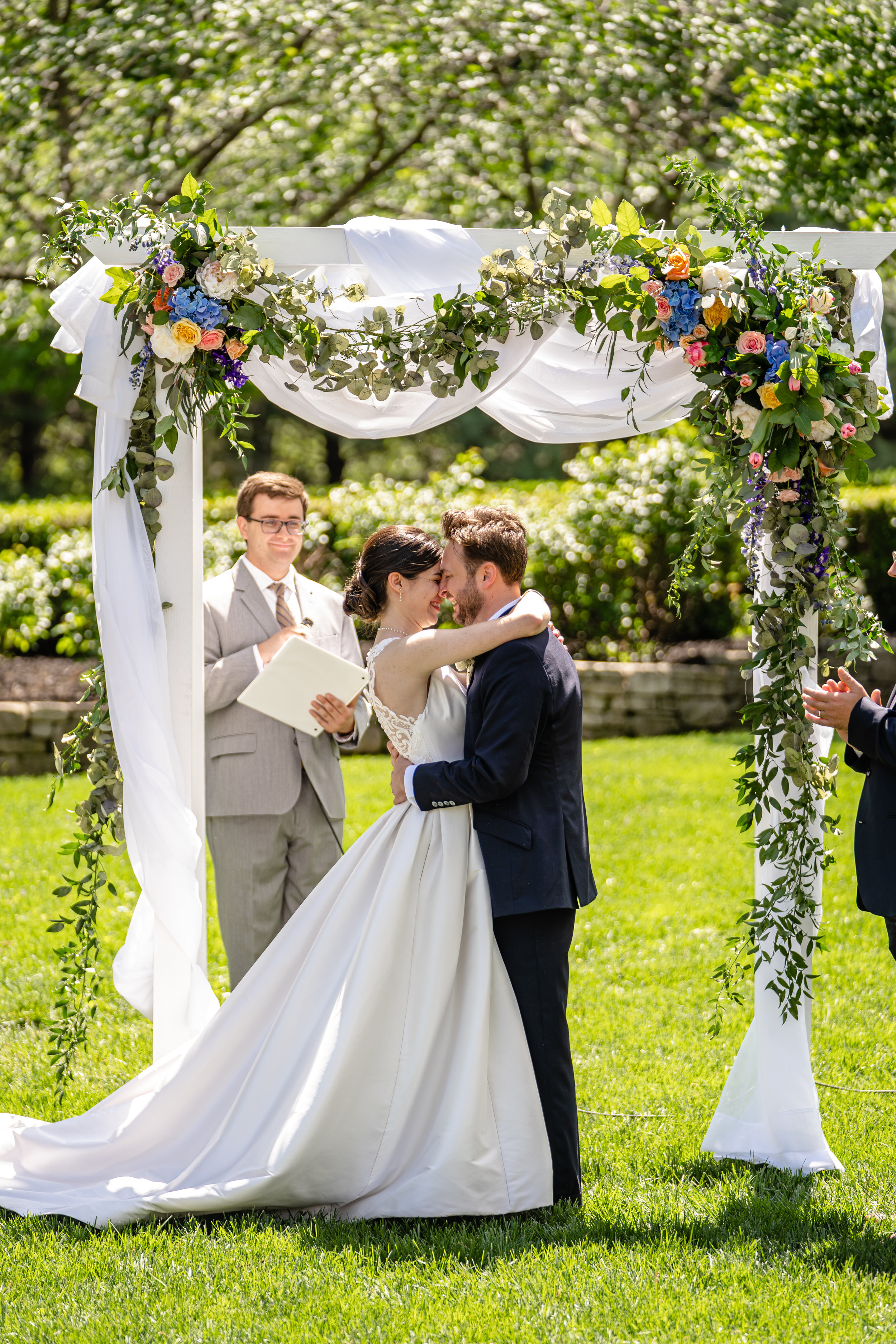 The couple embraces after their first kiss as husband and wife! Overjoyed, they hug and smile under the beautifully designed arbor from The Flower Merchant coordinated by their intentional and creative wedding planner.