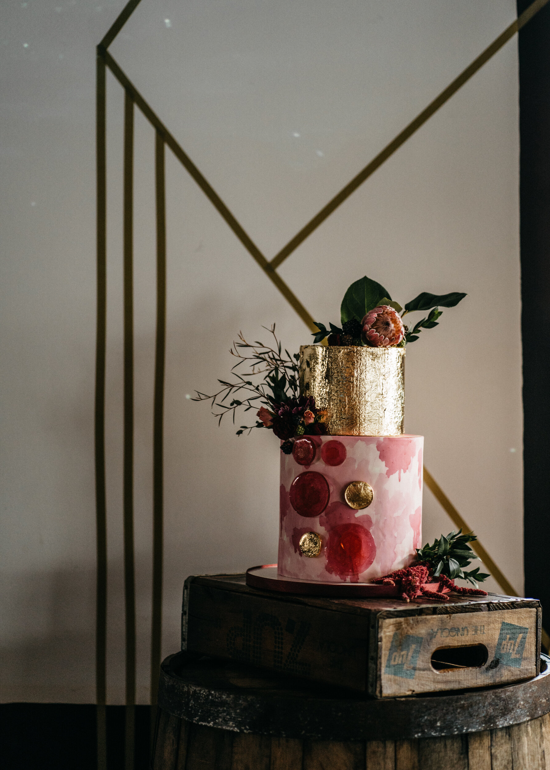Gold designs along a Missouri Spirits Distillery wall and on cake by Charity Fent Cake Design - Industrial Wedding Inspiration with Destination Wedding Planner Unions With Celia and Destination Photographer Sean Reid Photography.