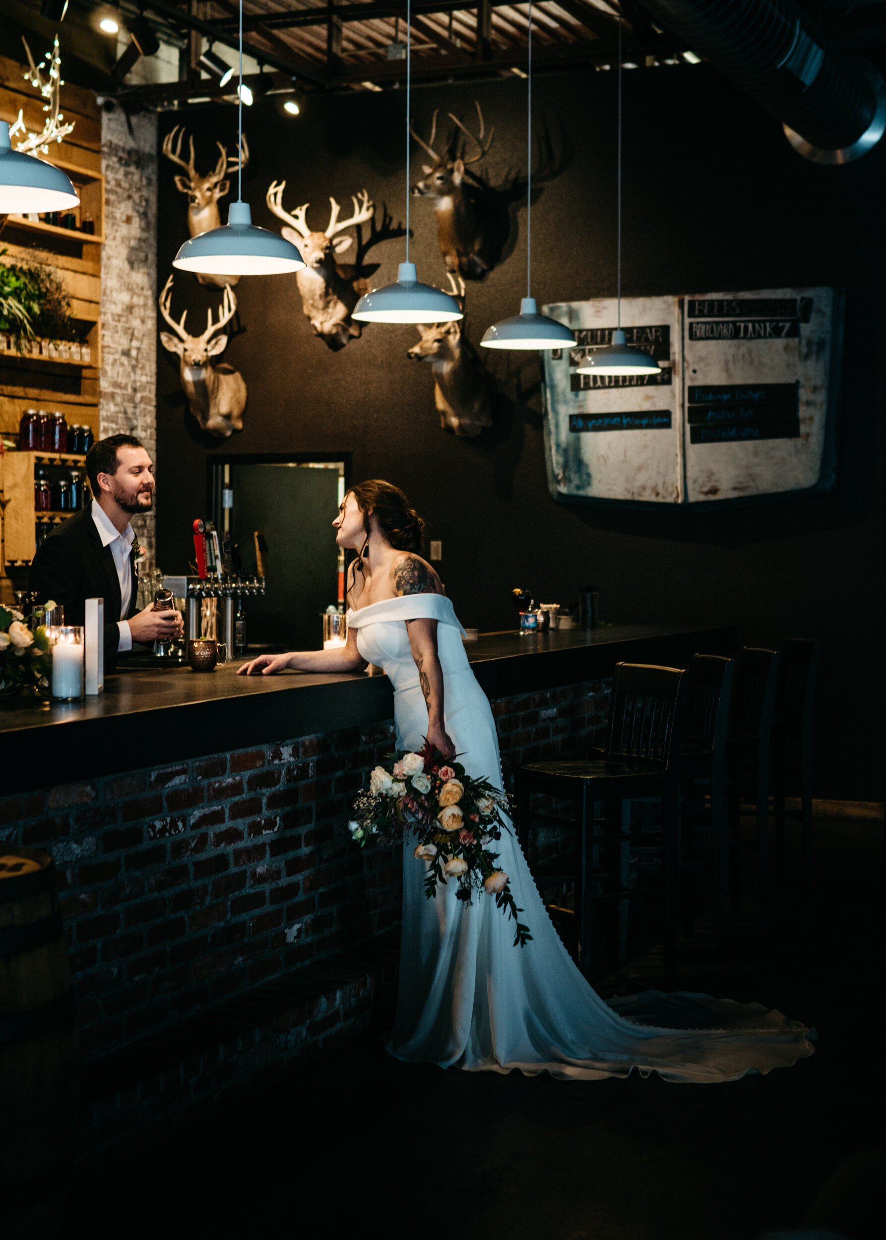 Groom makes his bride a drink at the Missouri Spirits Bar during their moody, romantic wedding - Industrial Wedding Inspiration with Destination Wedding Planner Unions With Celia and Sean Reid Photography
