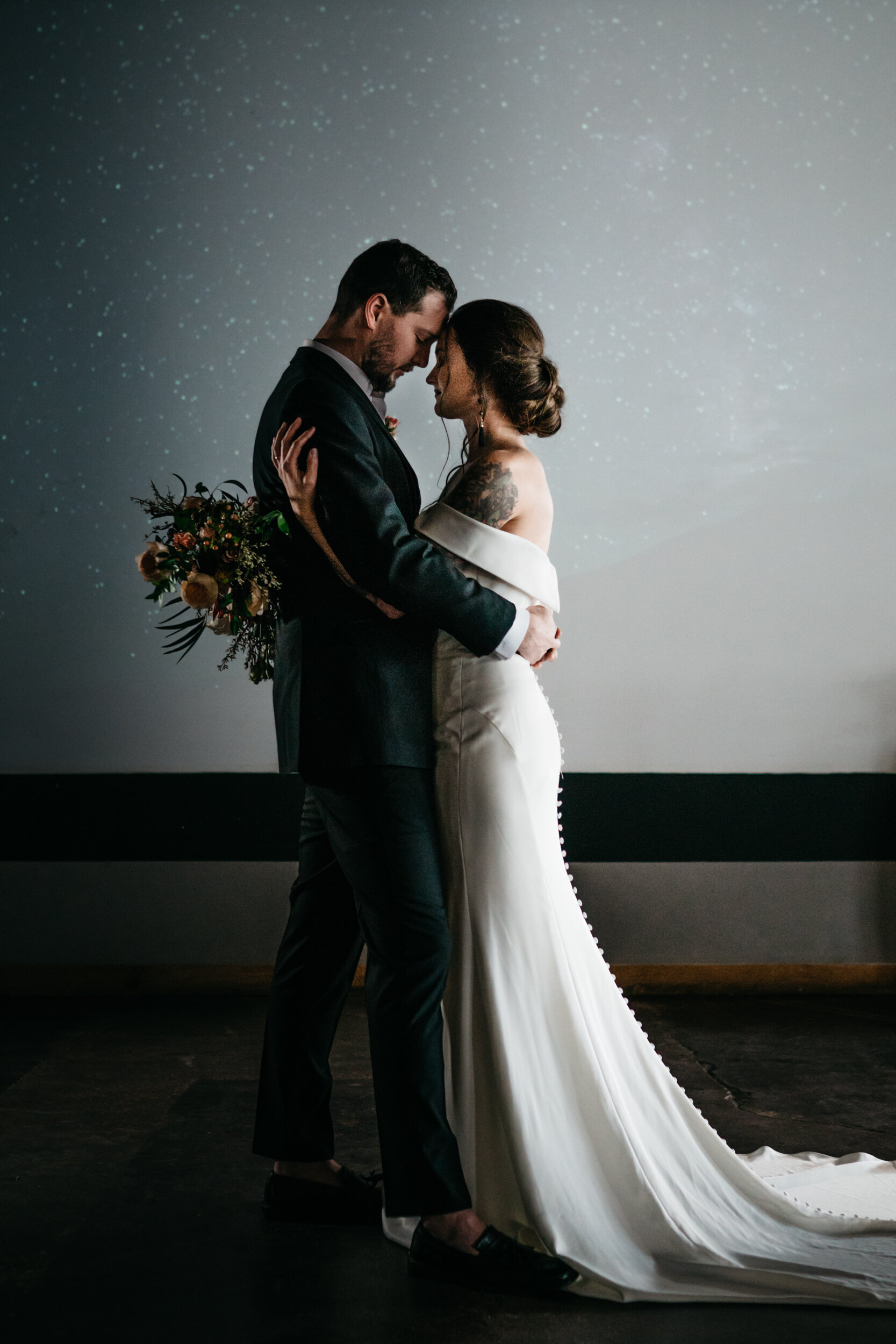 Modern couple projects a starry night sky behind them during the first dance at Missouri Spirits. Sean Reid Photography. Romantic bouquet by Queen City Blooms. Industrial Wedding Inspiration with Creative Wedding Planner Unions With Celia