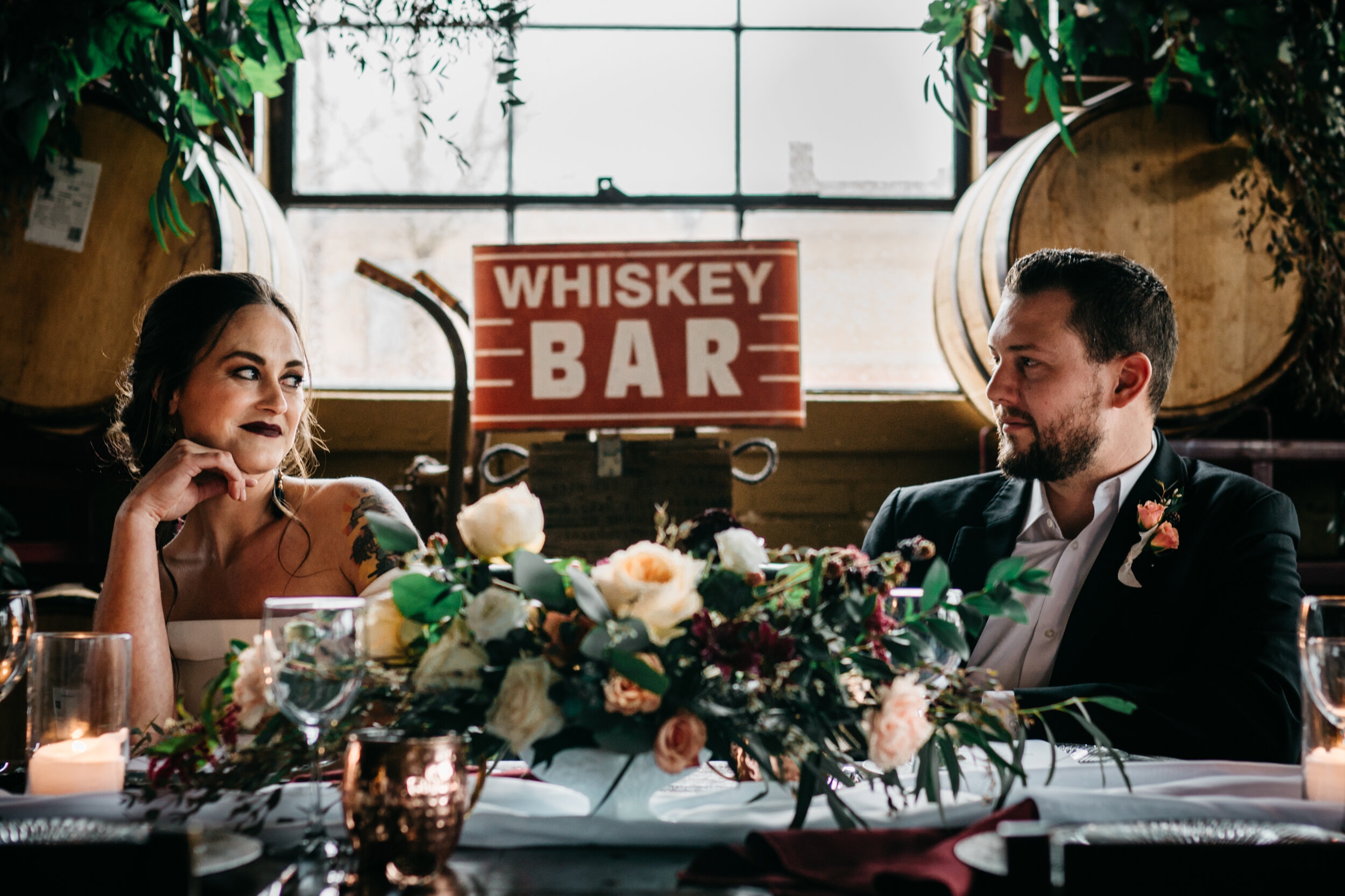 Cozy tablescape with glowing candles, romantic florals from Queen City Blooms and metals on a cool, wintery day. Missouri Spirits venue. Industrial Wedding Inspiration with Creative Wedding Planner Unions With Celia. Sean Reid Photography.