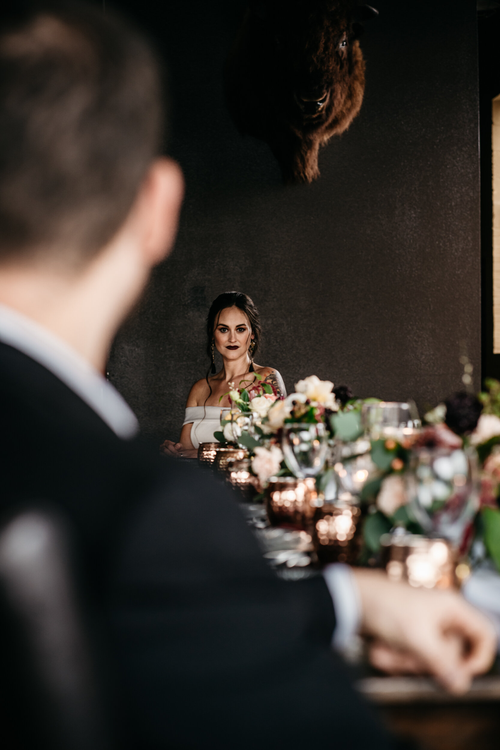 Bride sitting at edge of long table for moody, romantic distillery wedding designed by wedding planner Unions With Celia at Missouri Spirits. Photographed by Sean Reid.