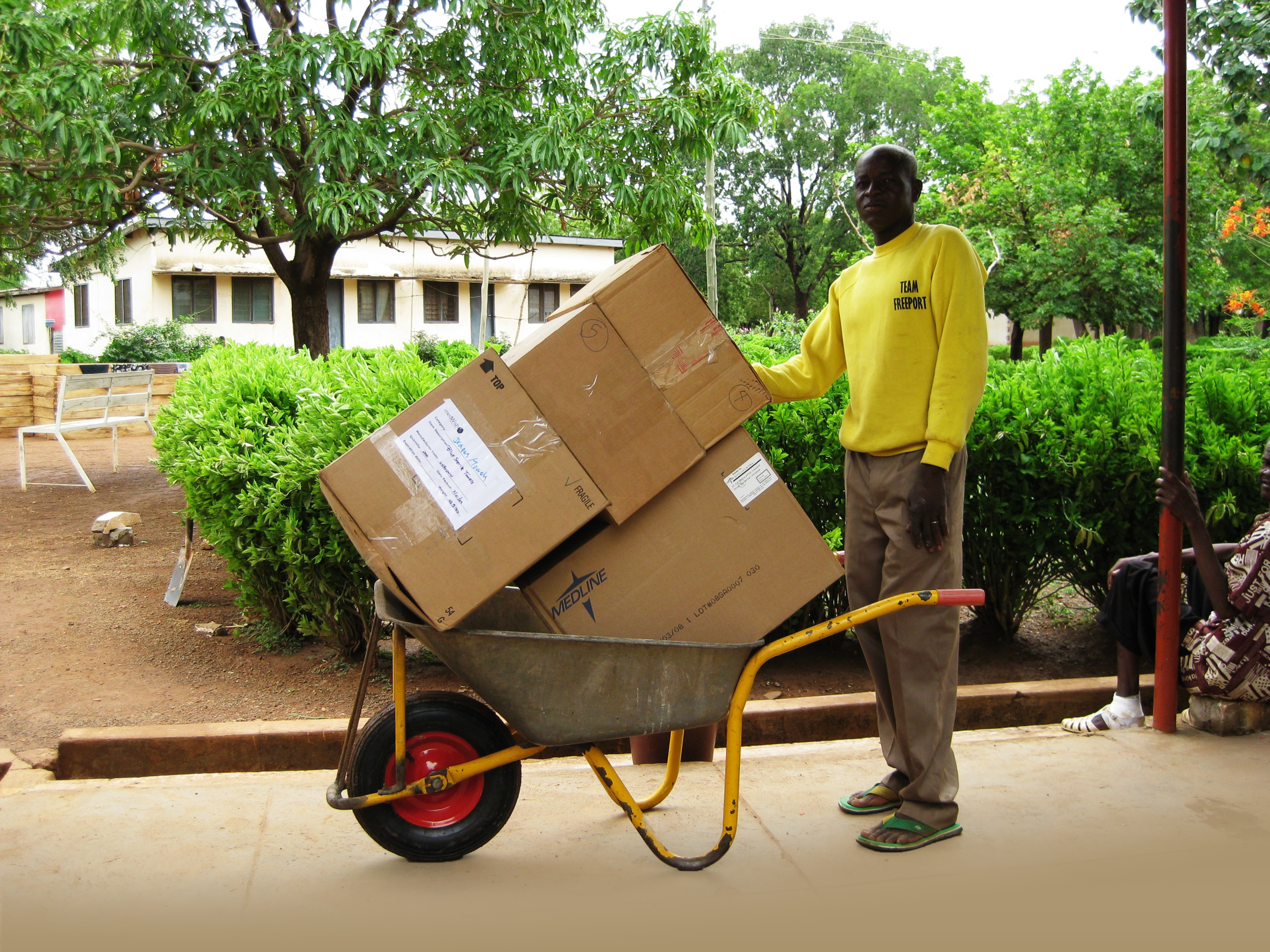 Transporting Donated Supplies with Wheelbarrow - Lawra 2.png