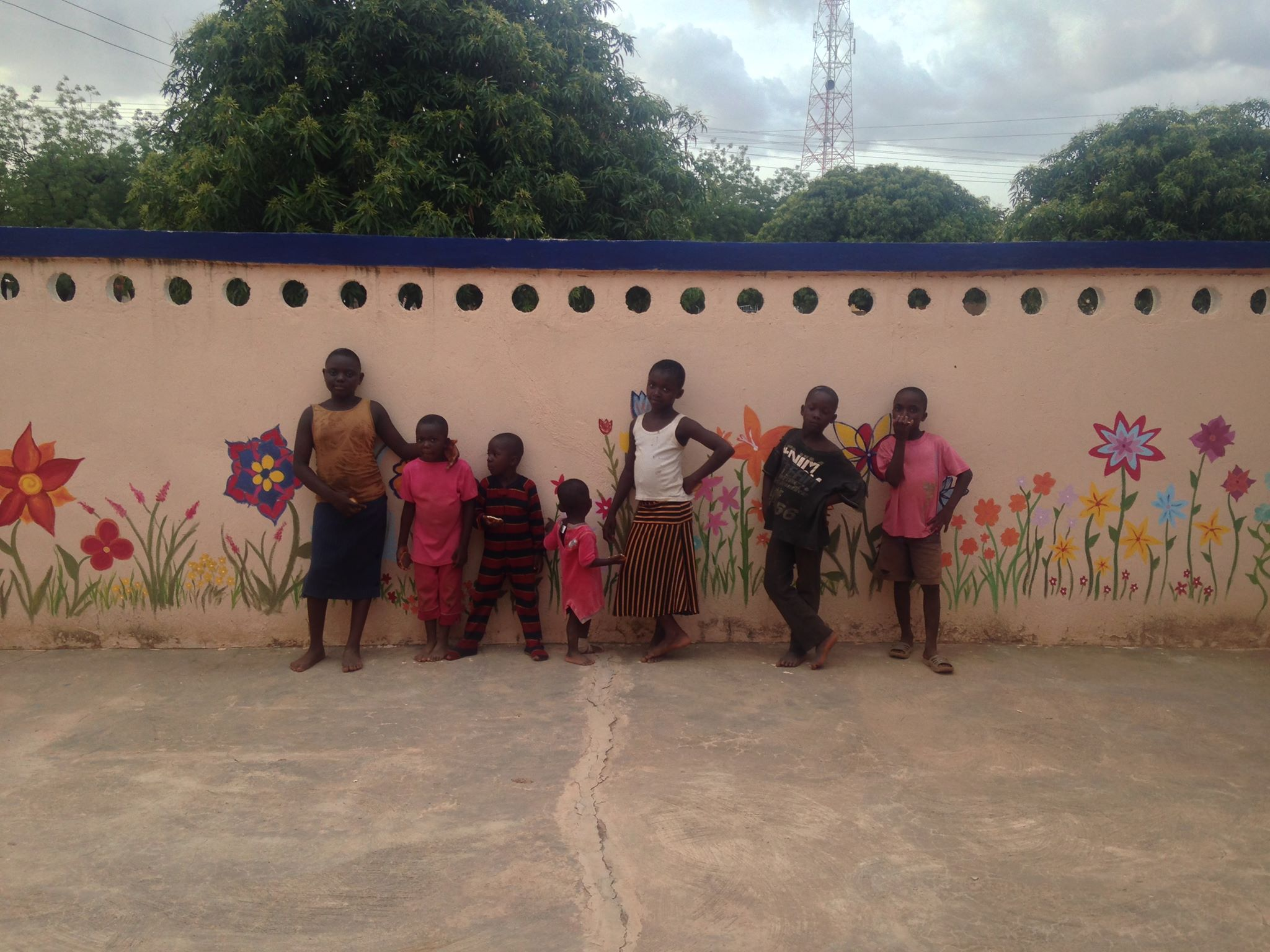 Children gathered in front of the mural Project Heal painted the Lawra Nutrition Center