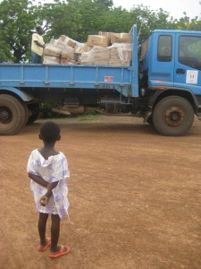 A girl in Lawra, Ghana watches as supplies from a shipment are unloaded and taken to the Lawra District Hospital