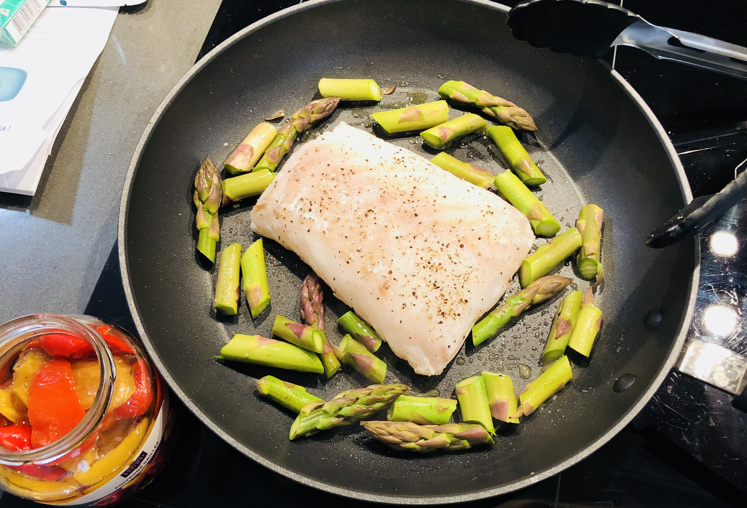 Fish frying surrounded by Asparagus (fish seasoned on second side while cooking)