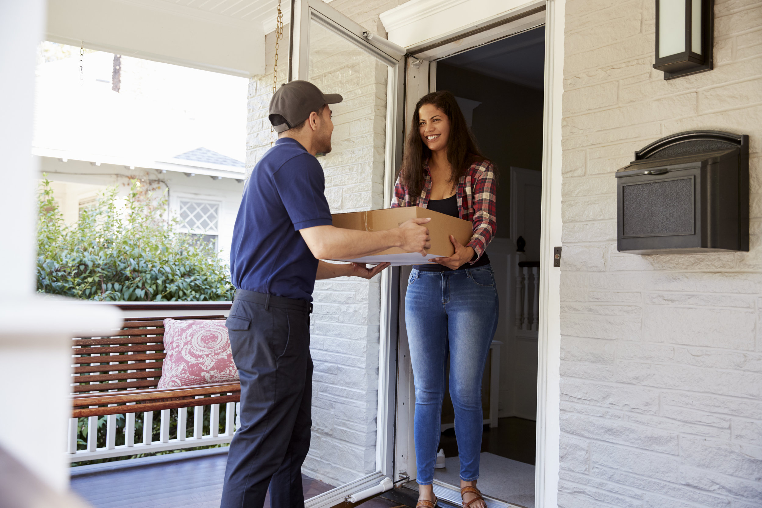 courier-delivering-package-to-woman-at-home-PR78SK6.jpg