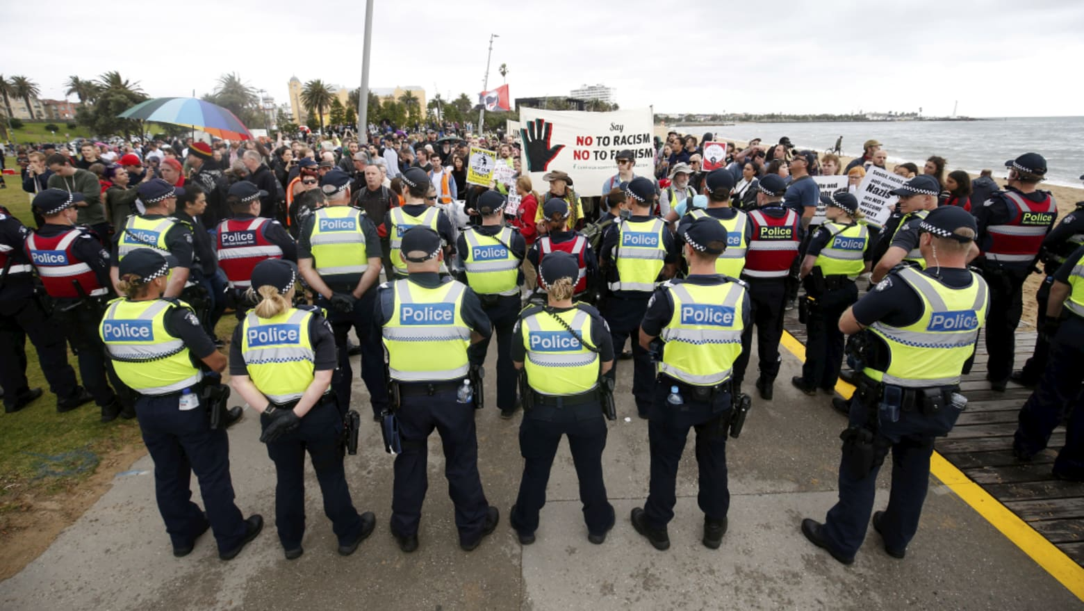 Police stand between far-right and anti-racism protesters at the St Kilda rally. Credit:Darrian Traynor