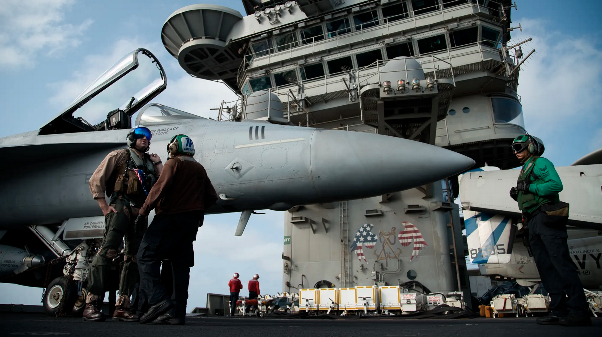 A pilot speaks to a crew member by an F/A-18 fighter jet on the deck of the USS Abraham Lincoln aircraft carrier in the Arabian Sea. Donald Trump has threatened Iran with 'obliteration'. Credit:AP