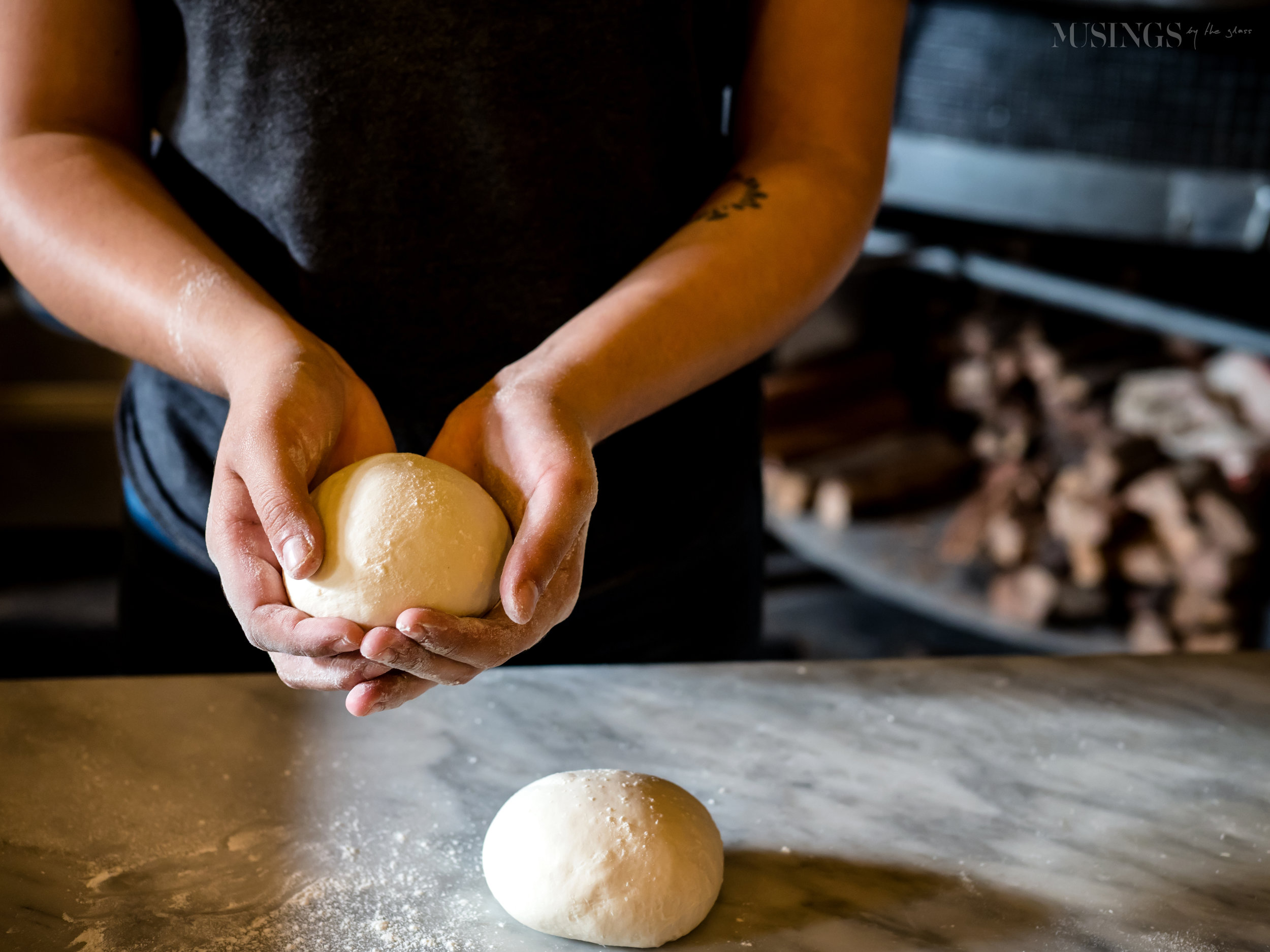 Favored Photos Reflective - Snap a Photo Make a Friend - Female Employee rolls pizza dough at Brick Fire Tavern in Chinatown Honolulu Hawaii