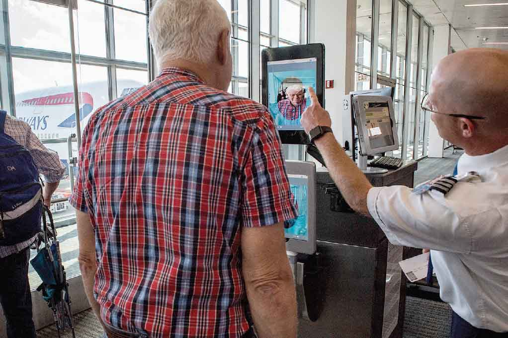 Figure. A Transportation Security Administration (TSA) screener uses a biometric facial recognition scanner on a traveler at Washington Dulles International Airport.