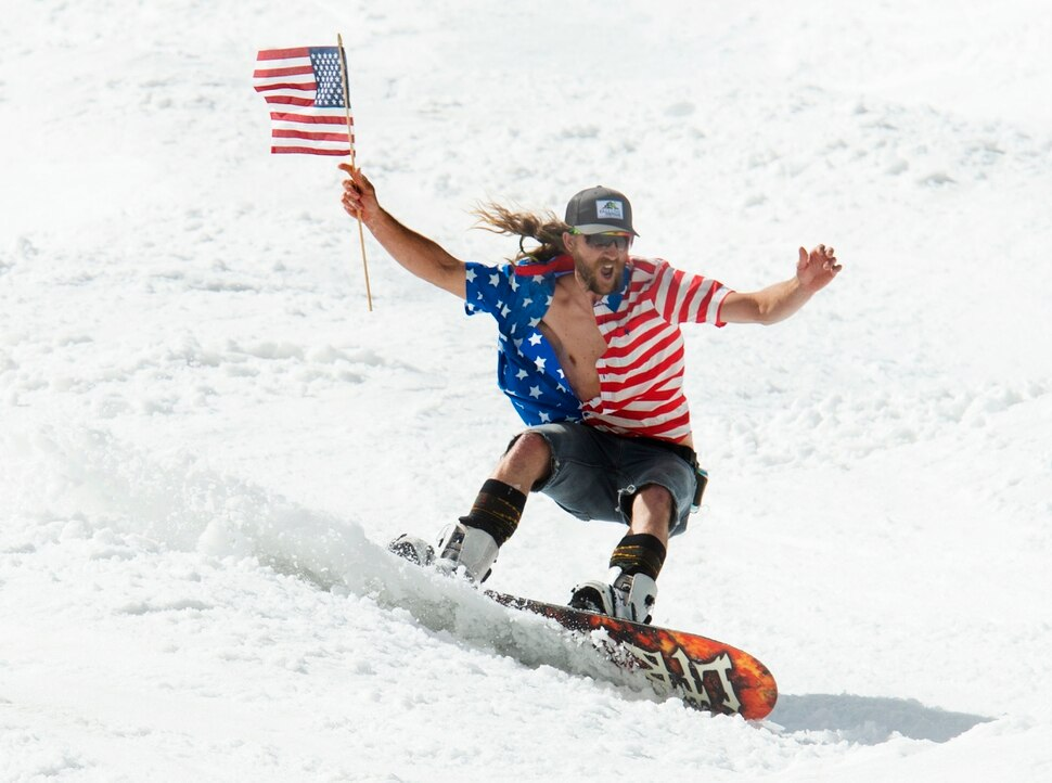 Image by Rick Egan | The Salt Lake Tribune. - James Perry, from Salt Lake City, makes his way down the hill while waving a flag and dressed for the Fourth of July on the last ski day of the year at Snowbird Ski resort on Thursday, July 4, 2019.