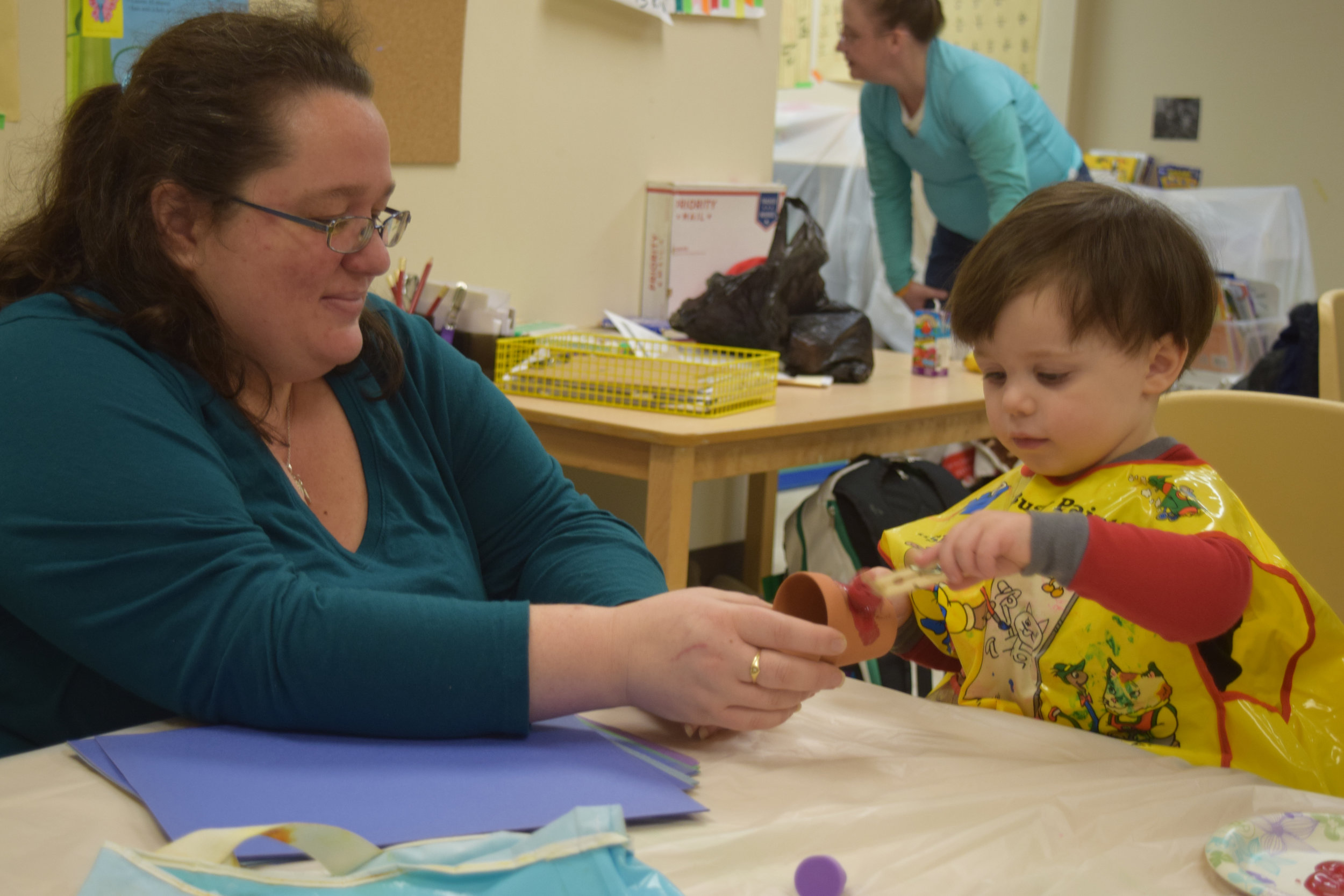 Candice Riggs holds a flower pot as her son, Jasper, paints it.