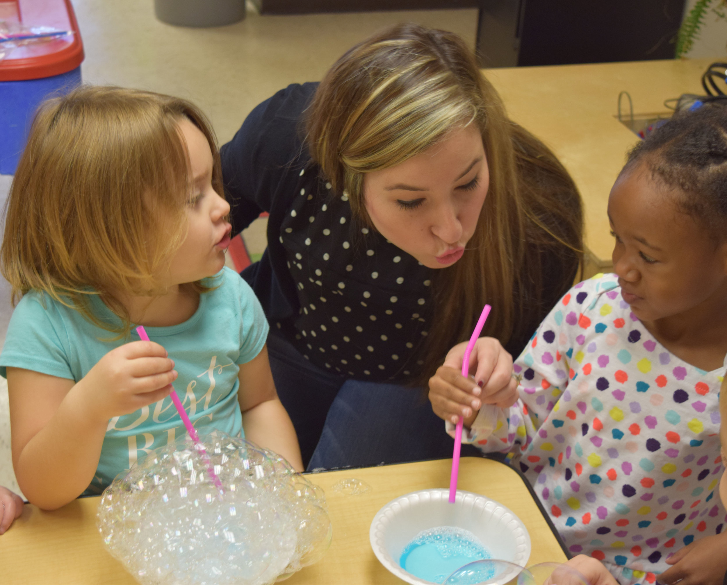 Volunteer Melissa Gamboa shows kids how to blow bubbles at the Children's Learning Center in Walled Lake.