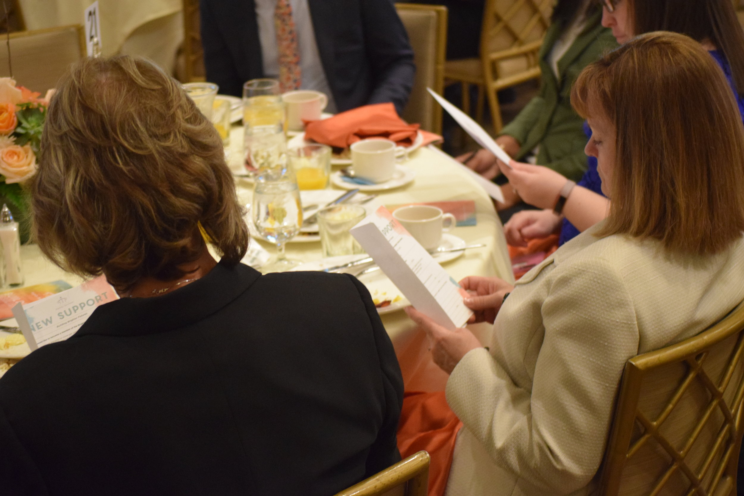 Breakfast attendees review pledge cards.