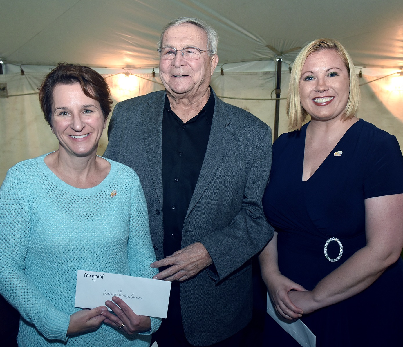 Kris Kasperski, director of Early Childhood Services, receives a Brooksie Way mini-grant from L. Brooks Patterson, chairman of the Brooksie Way Board of Directors, and Heidi McGlinnen, Director of Marketing and Foundation for McLaren Oakland. Photo taken by Vaughn Gurganian.