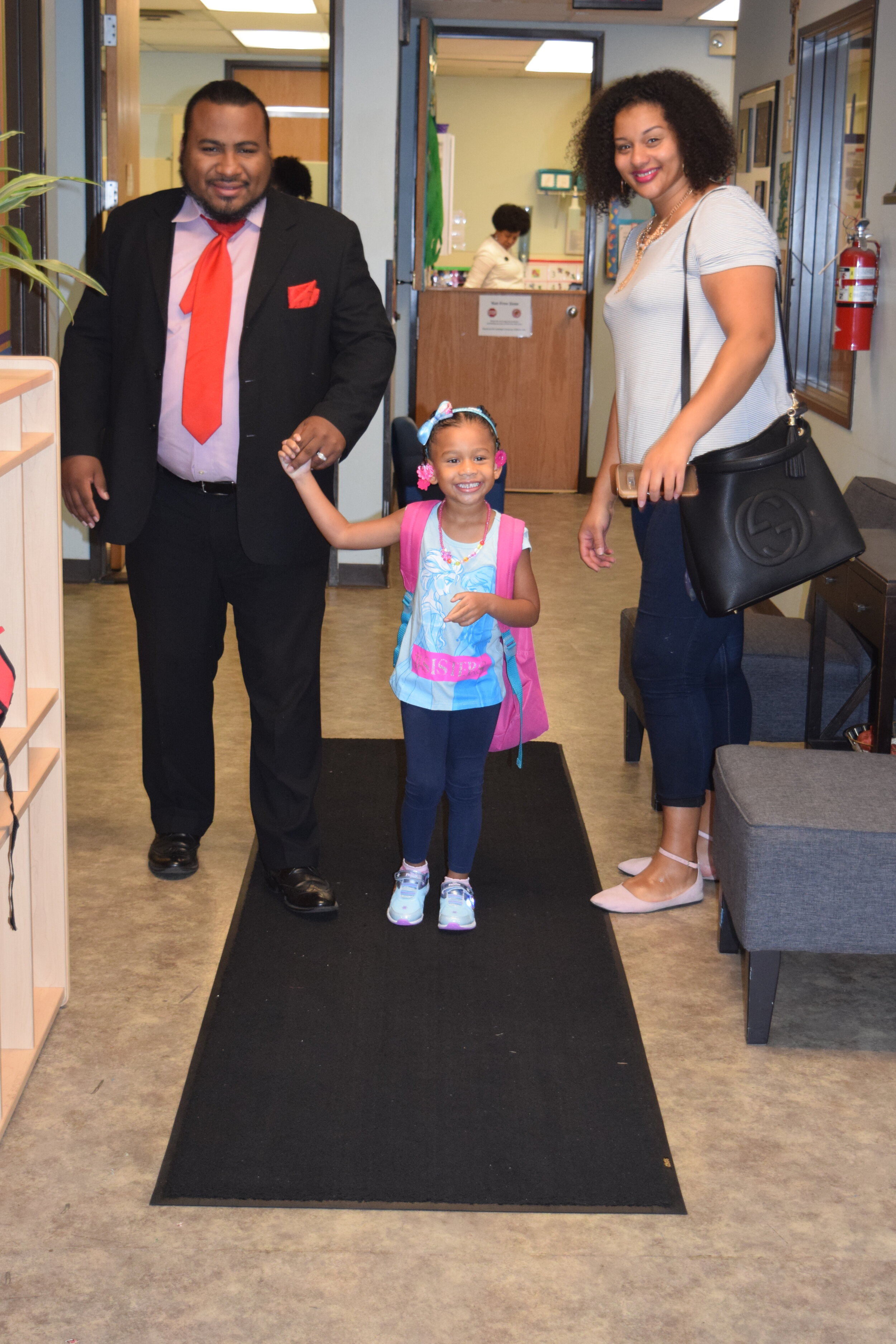 Desi (center) walks into the Children's Learning Center on her first day of preschool with her father, Dennis Thompson, and mother, Bonnie.