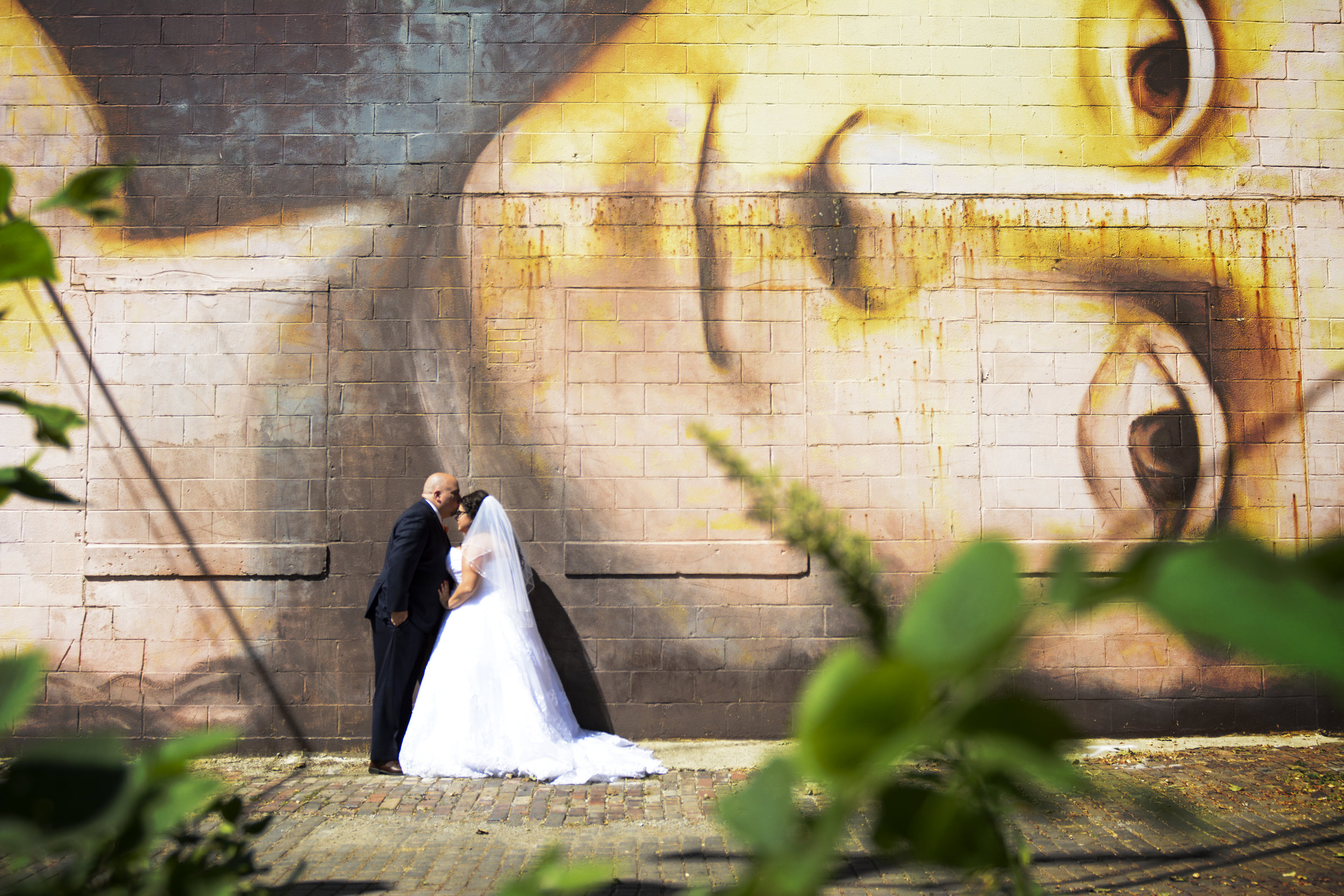 bride and groom kiss in front of mural in short north columbus on their wedding day