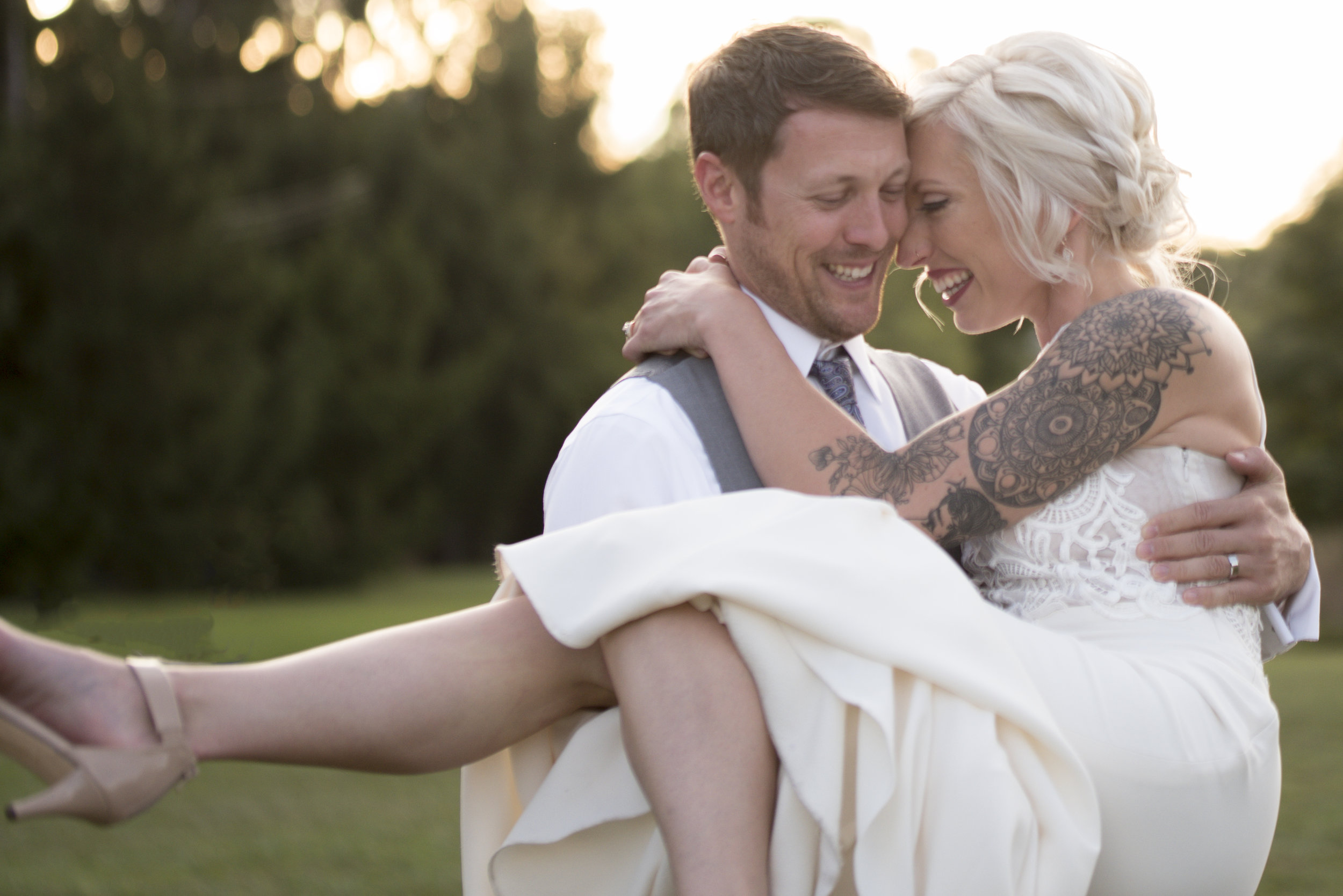 Groom carries bride during portrait on wedding day