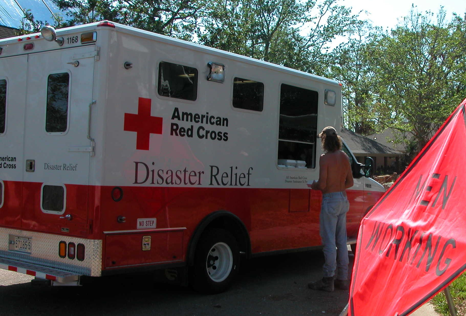 11. A resident of Waveland, Mississippi accepts a boxed meal from the American Red Cross four weeks after Hurricane Katrina decimated his community.