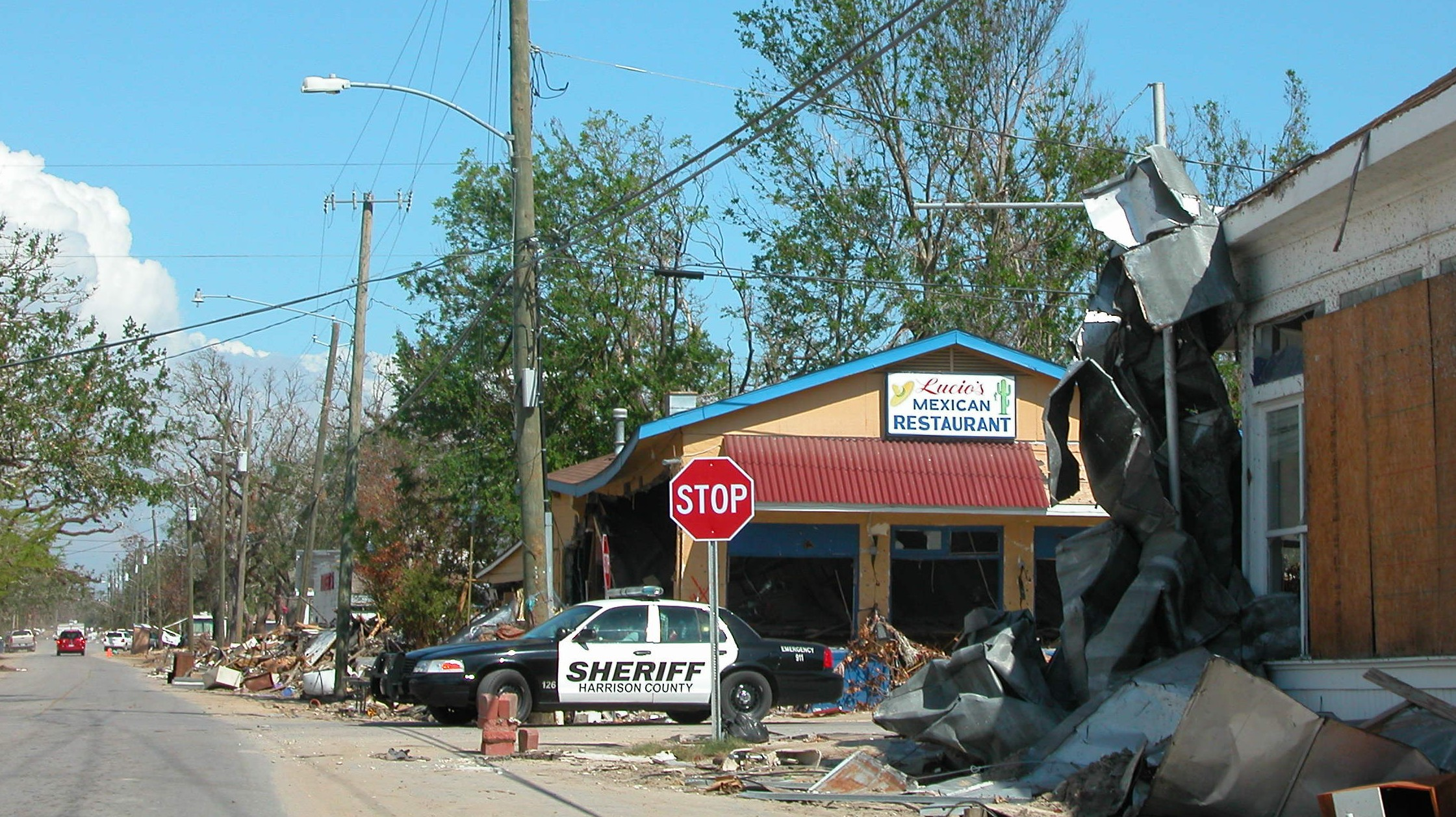 "18. Photo shows the heightened police presence in Long Beach, Mississippi in the aftermath of Katrina. Note the trash and debris lining the roadways. ""I couldn't imagine facing the debris and devastation every single day. It was everywhere, and there was no escaping it."" - David Aft"