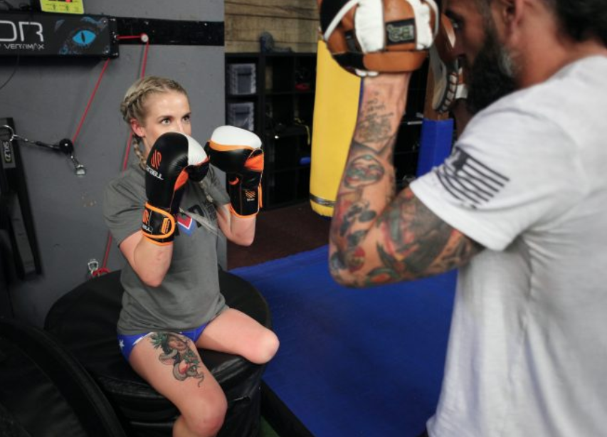 Veteran Kirstie Ennis —who had part of her left leg amputated after injuries from a helicopter crash in Afghanistan—trains for her upcoming Mount Denali climb by boxing. (Gary DeJidas)