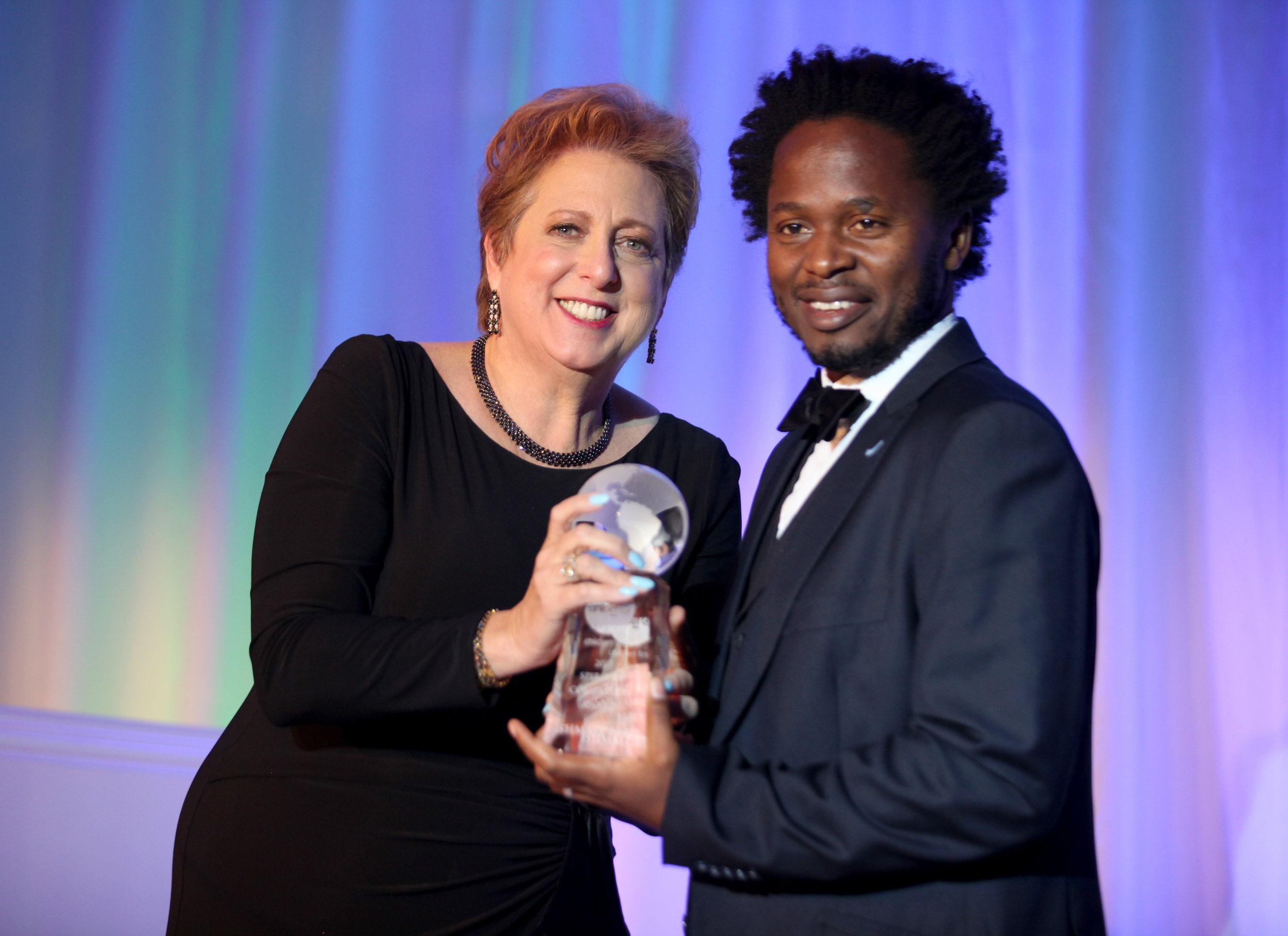 President & CEO Caryl Stern presenting the Spirit of Compassion Award to UNICEF Goodwill Ambassador Ishmael Beah (Photo by Getty Images)