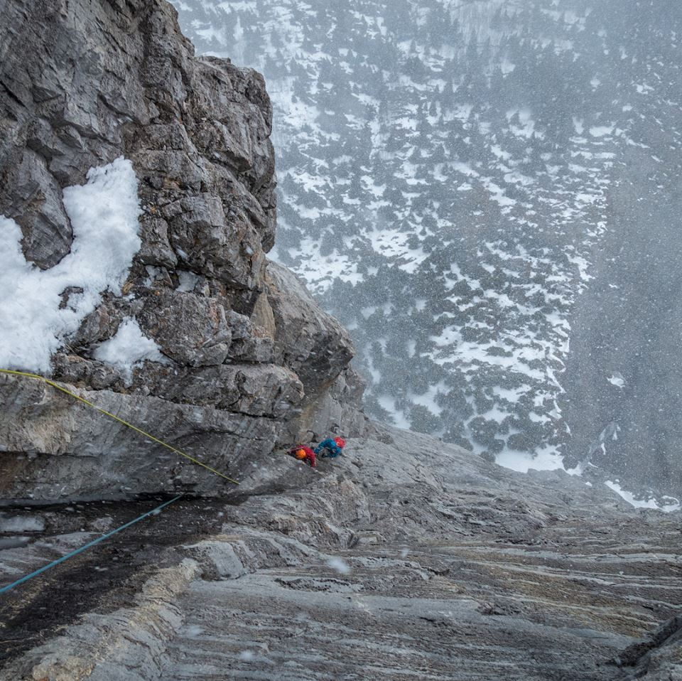 Looking back down the route Kahl Wall on Mt Yamnuska. The sheer rock face forces the air upwards resulting in the snow floating up past us rather than falling towards earth. Pretty cool stuff. Photo by Jaz Morris.